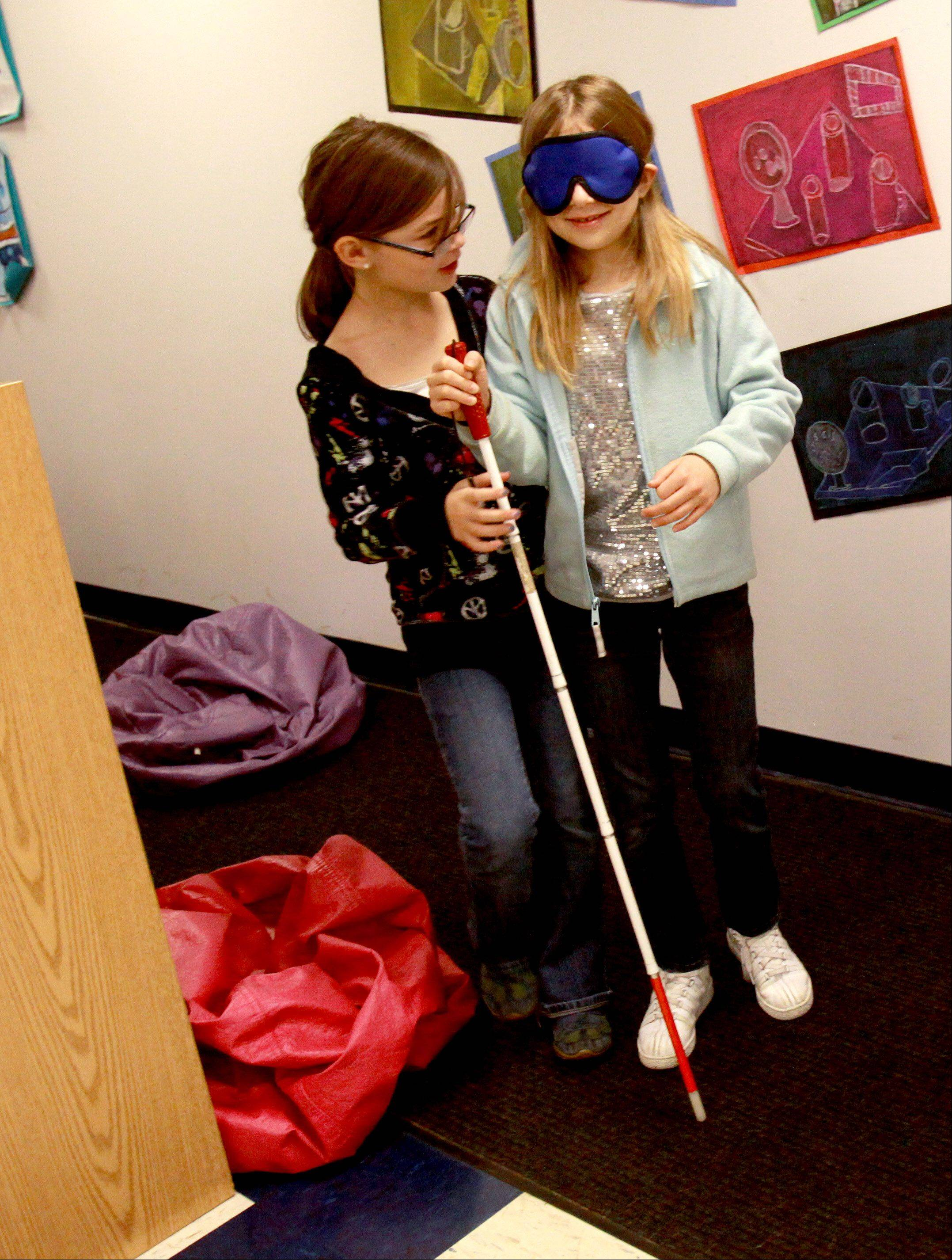 Grace Elliott, left, helps fellow third-grader Jane Sottrel as she makes her way with a blindfold as the Western DuPage Special Recreation Association's Disability Awareness Program visits Wiesbrook School in Wheaton.