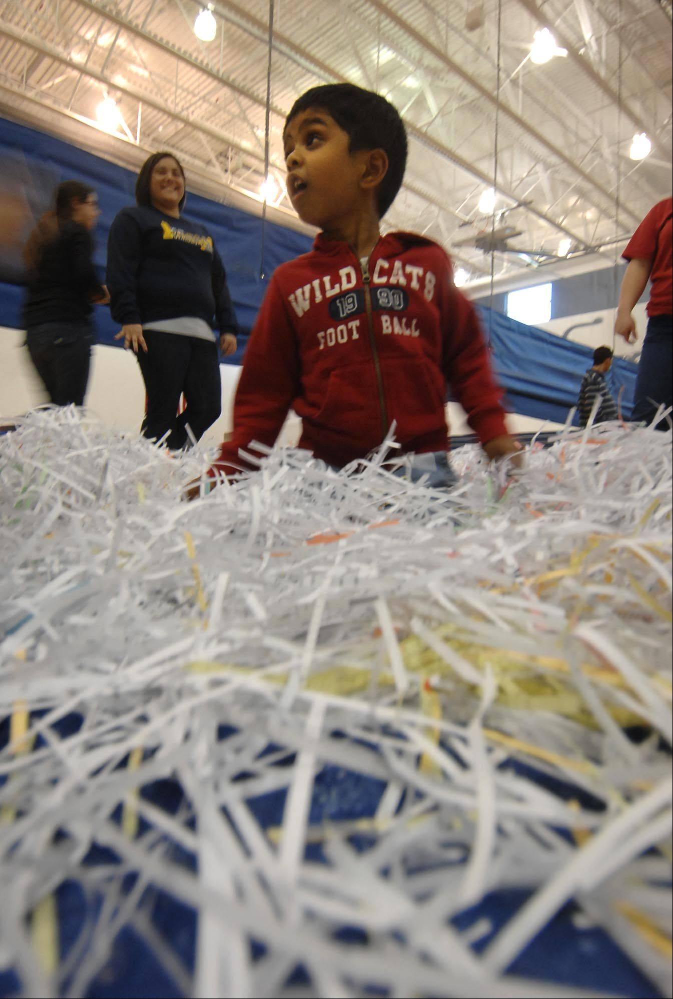 Sourya Palepu, 4, looks for candy and plastic eggs in shredded paper Thursday at an Adaptive Spring Holiday Egg Hunt at Kenyon Woods Middle School in South Elgin. The egg hunt is designed to meet the needs of children of all abilities and promotes hand-eye coordination. The South Elgin Parks and Recreation Department sponsors the annual event. He is from Aurora.