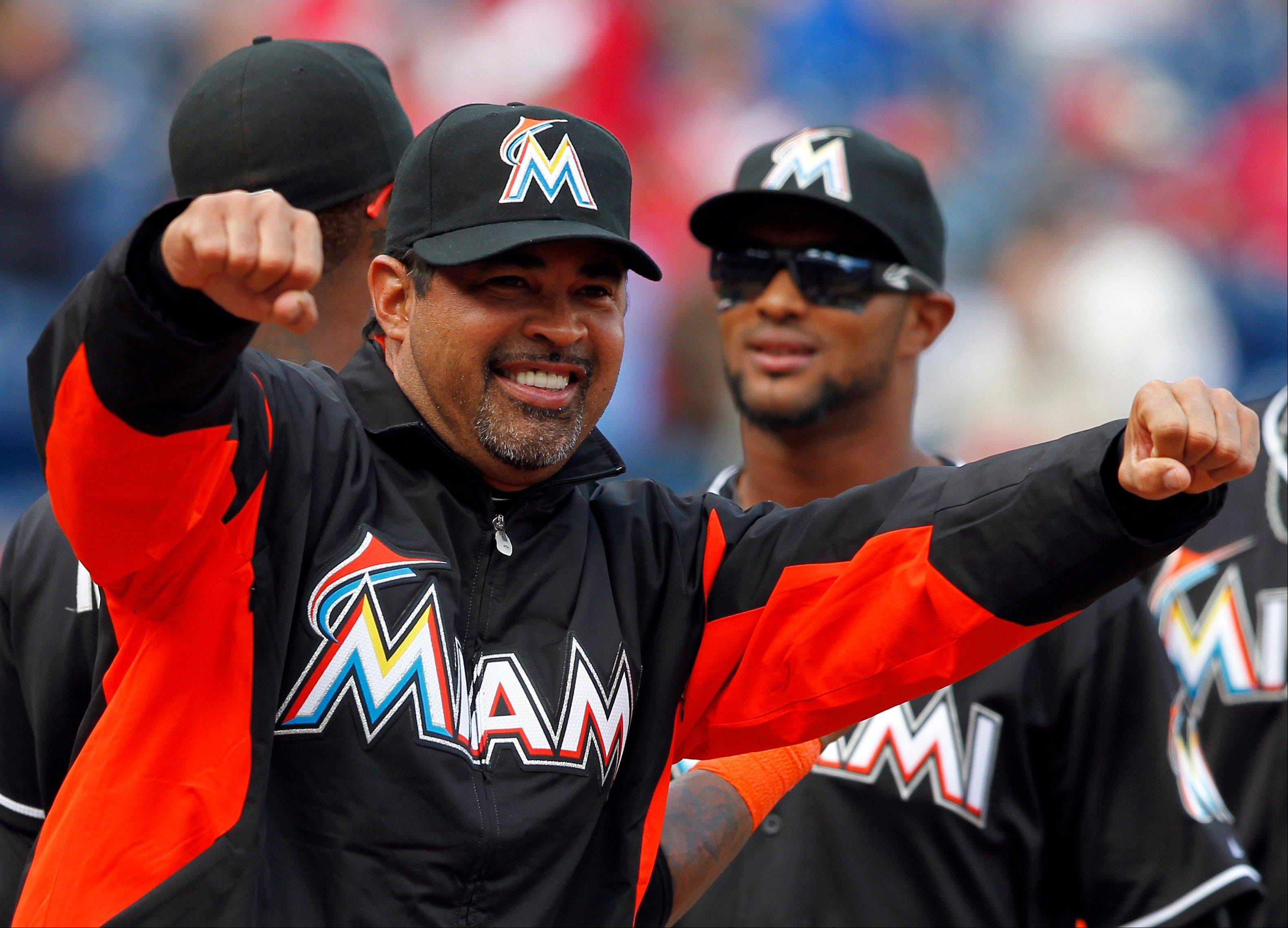 Miami Marlins manager Ozzie Guillen, left, gestures during introductions before the home opener baseball game with the Philadelphia Phillies Monday, April 9, 2012, in Philadelphia.