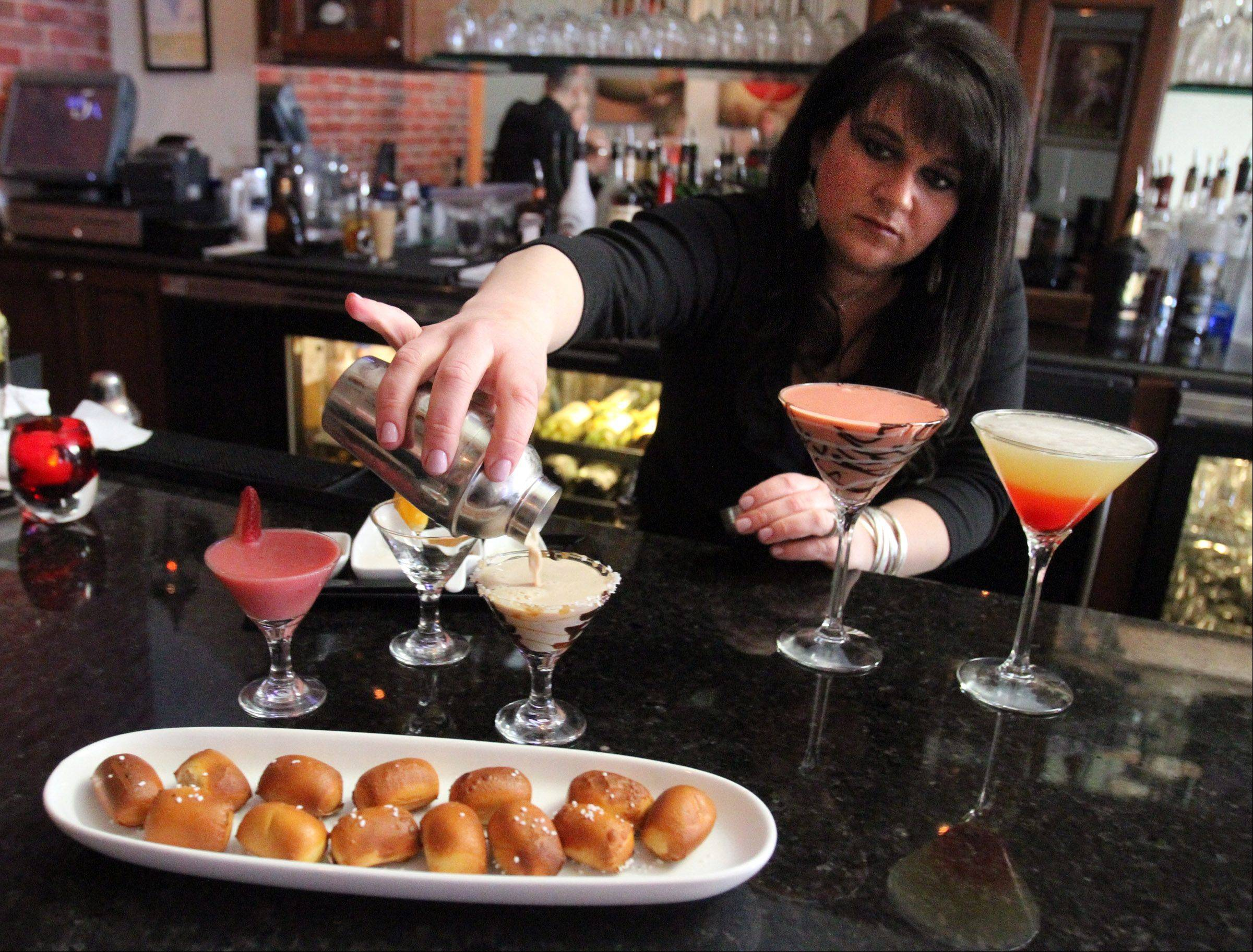 Bartender Shannon Longabaugh pours a mini salt-carmel-mocha martini with pretzel bites in the foreground at Strawberry Moon martini bar in Wauconda.
