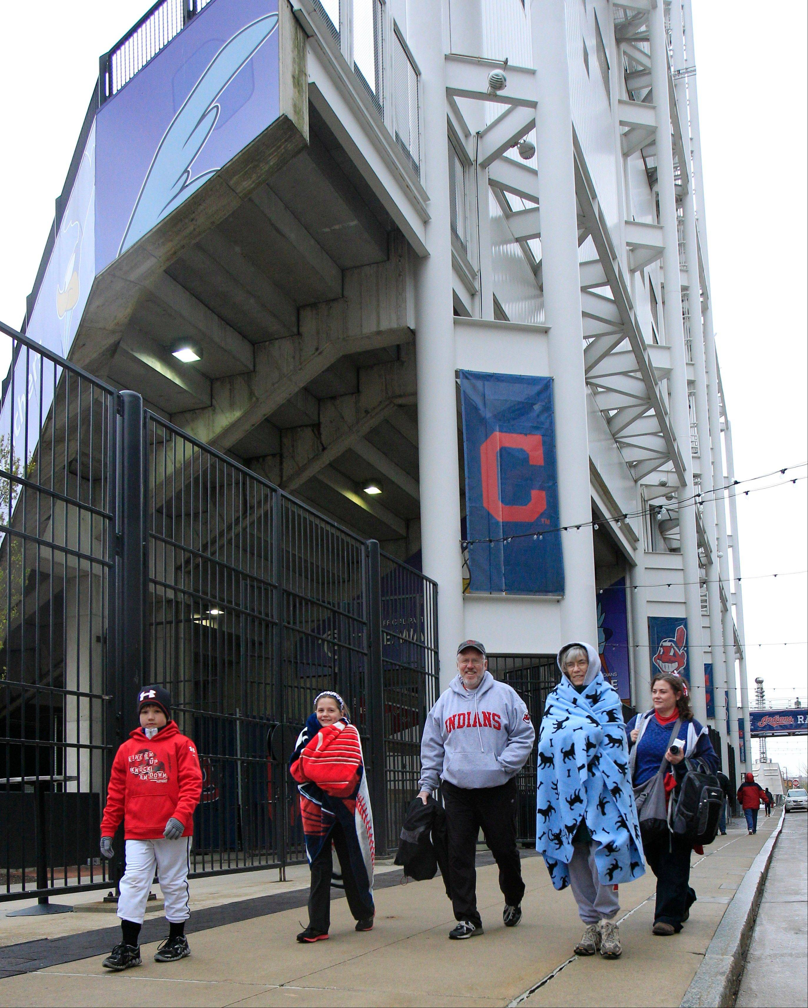 Grant, left to right, and Anna Craig, Rob and Pat Rose and Mickey Craig walk past Progressive Field all bundled up ready for a baseball game between the Chicago White Sox and the Cleveland Indians Tuesday, April 10, 2012, in Cleveland. The game was postponed due to adverse weather conditions.