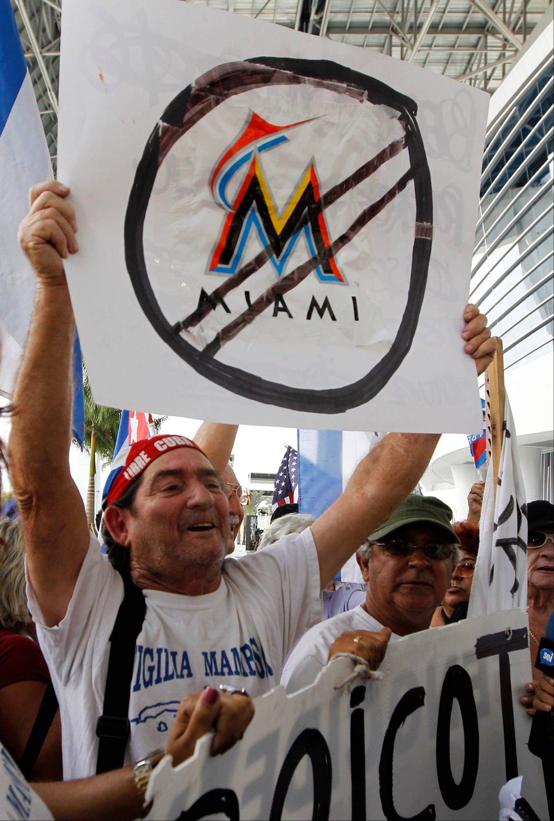 Protestors hold signs outside Marlins Stadium in Miami, where Marlins manager Ozzie Guillen was speaking at a news conference on Tuesday. Guillen has been suspended for five games because of his comments about Fidel Castro. He has again apologized and says he accepts the punishment.