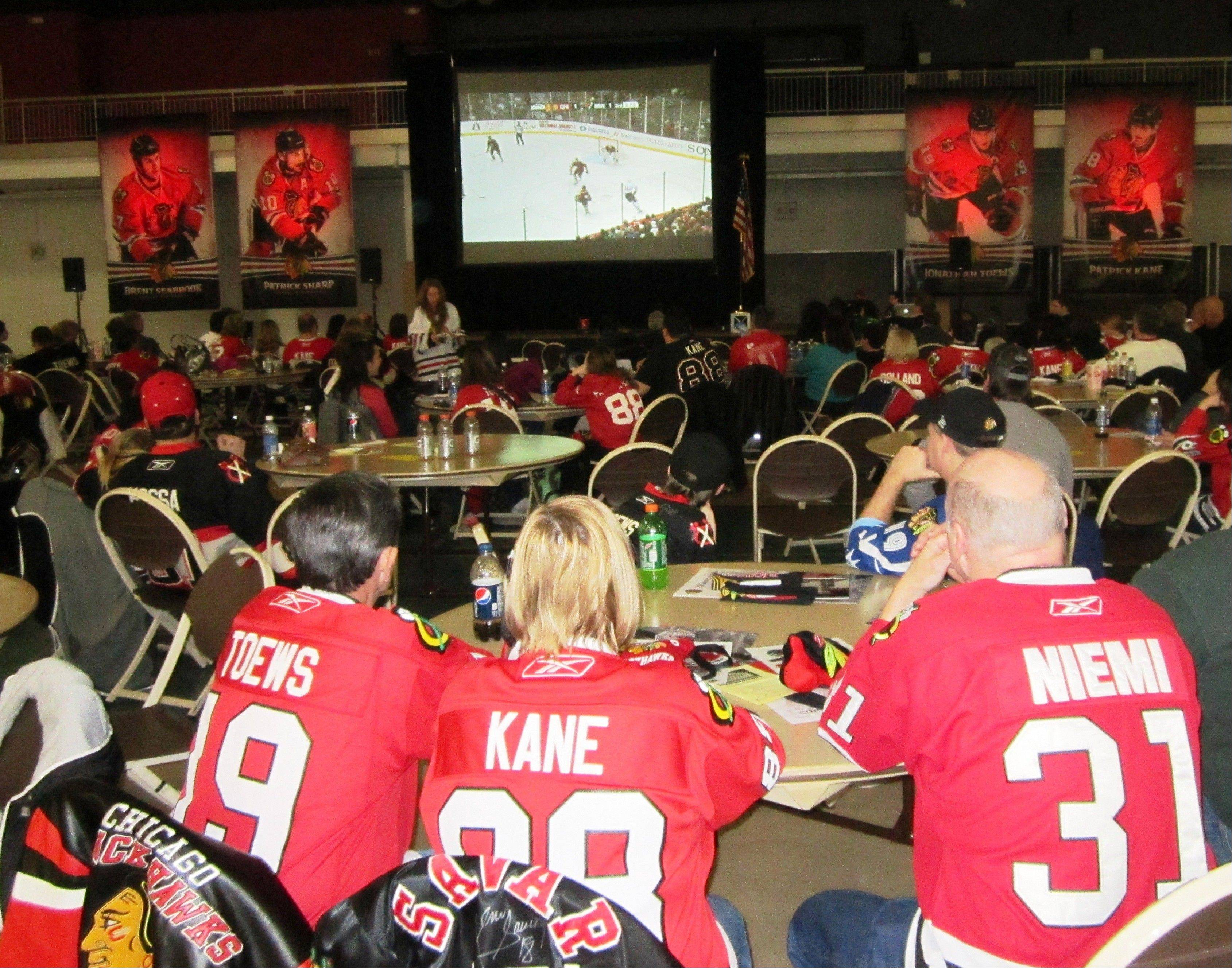 Jersey-wearing Blackhawks fans enjoy game action between the Blackhawks and Minnesota Wild on the big screen during the Blackhawks' Roadwatch Party at the Libertyville Sports Complex last Thursday.