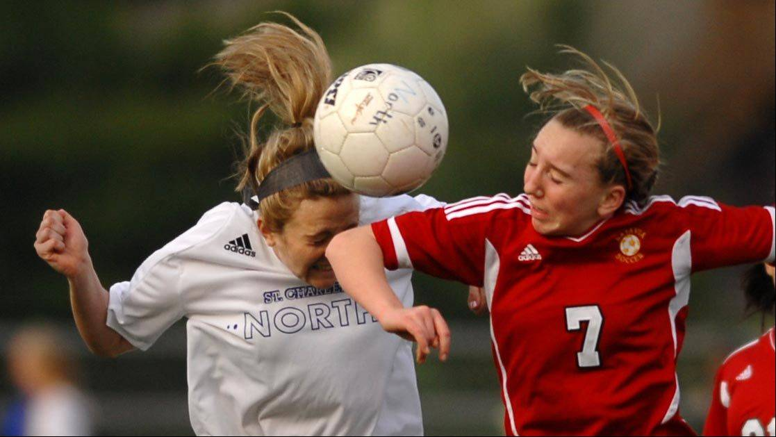 St. Charles North's Amanda Soukup takes an elbow to her head from Batavia's Alexis Bryl Tuesday in St. Charles.