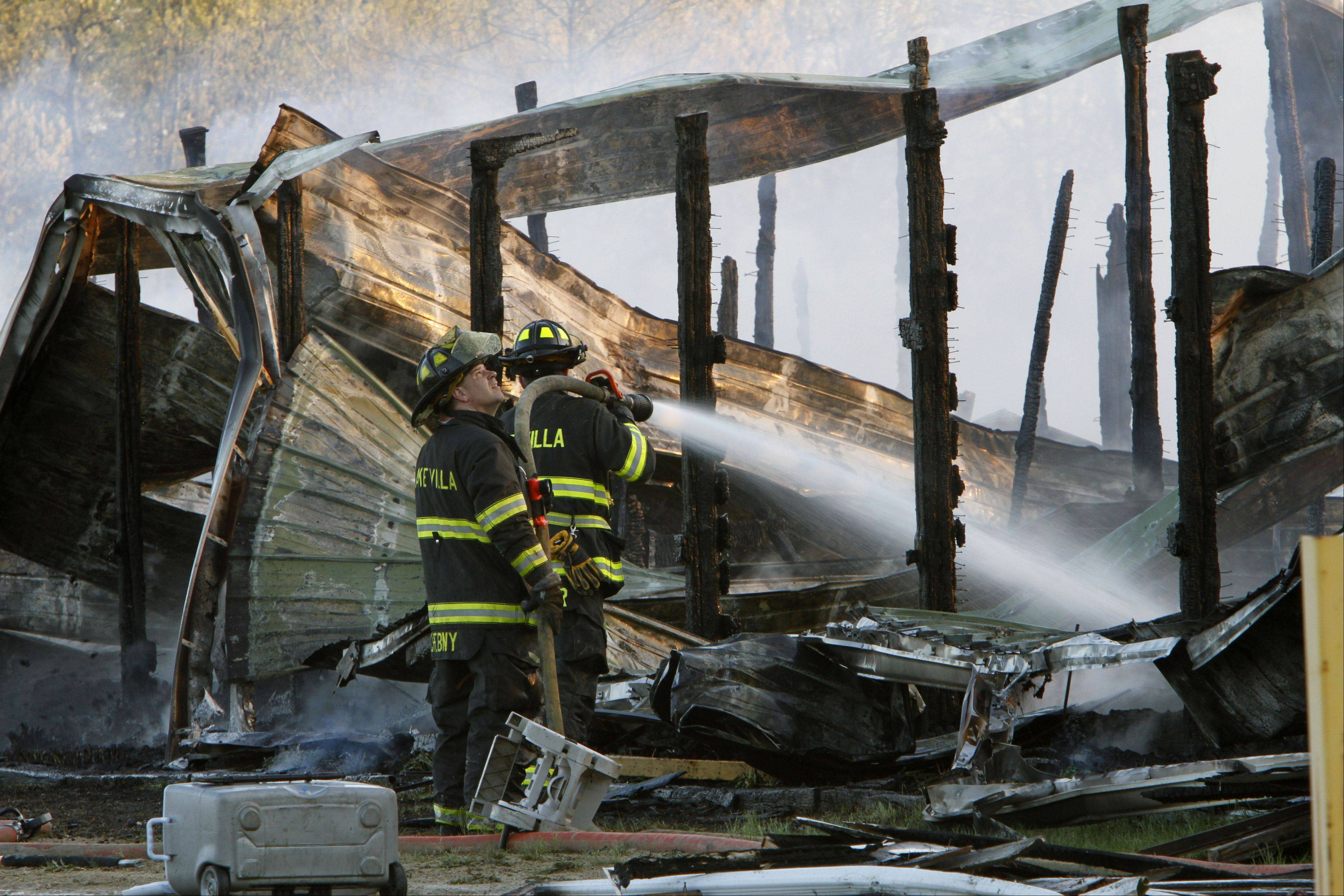 Lake Villa firefighters work to extinguish a fire at Black Tie Stable in McHenry Wednesday evening. The five-alarm fire destroyed the facility. Fire companies from throughout the area were on hand to help.