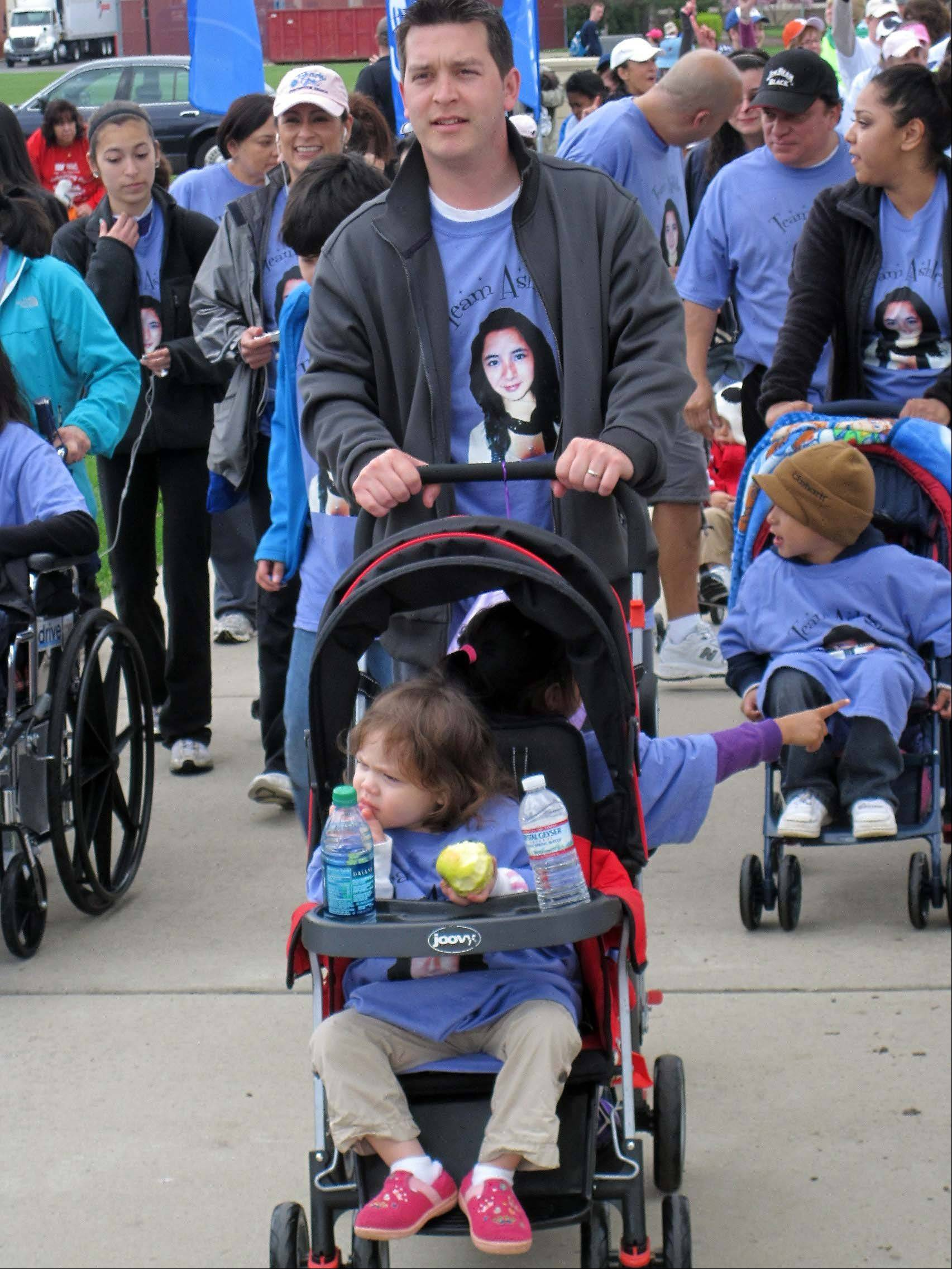 Ryan Quimby of Algonquin walked last year at the American Cancer Society's Walk & Roll in Elgin to support Ashley Garza, 13, pictured on his shirt. Garza died Tuesday from cancer.