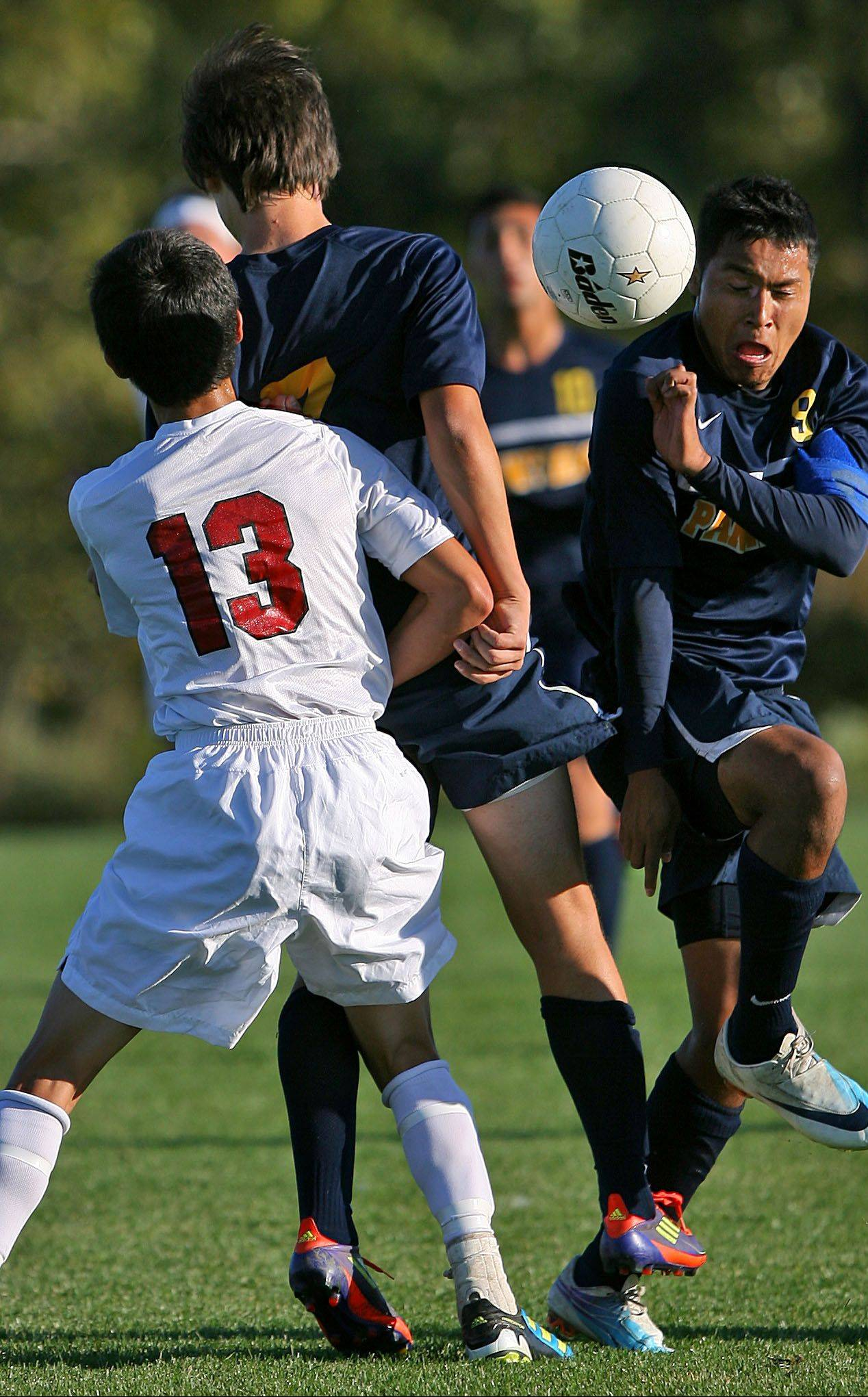 Antioch's Joshua Hallett, left, and Round Lake's Mauricio Salgado, center, and Jordi Rubio battle for a ball.