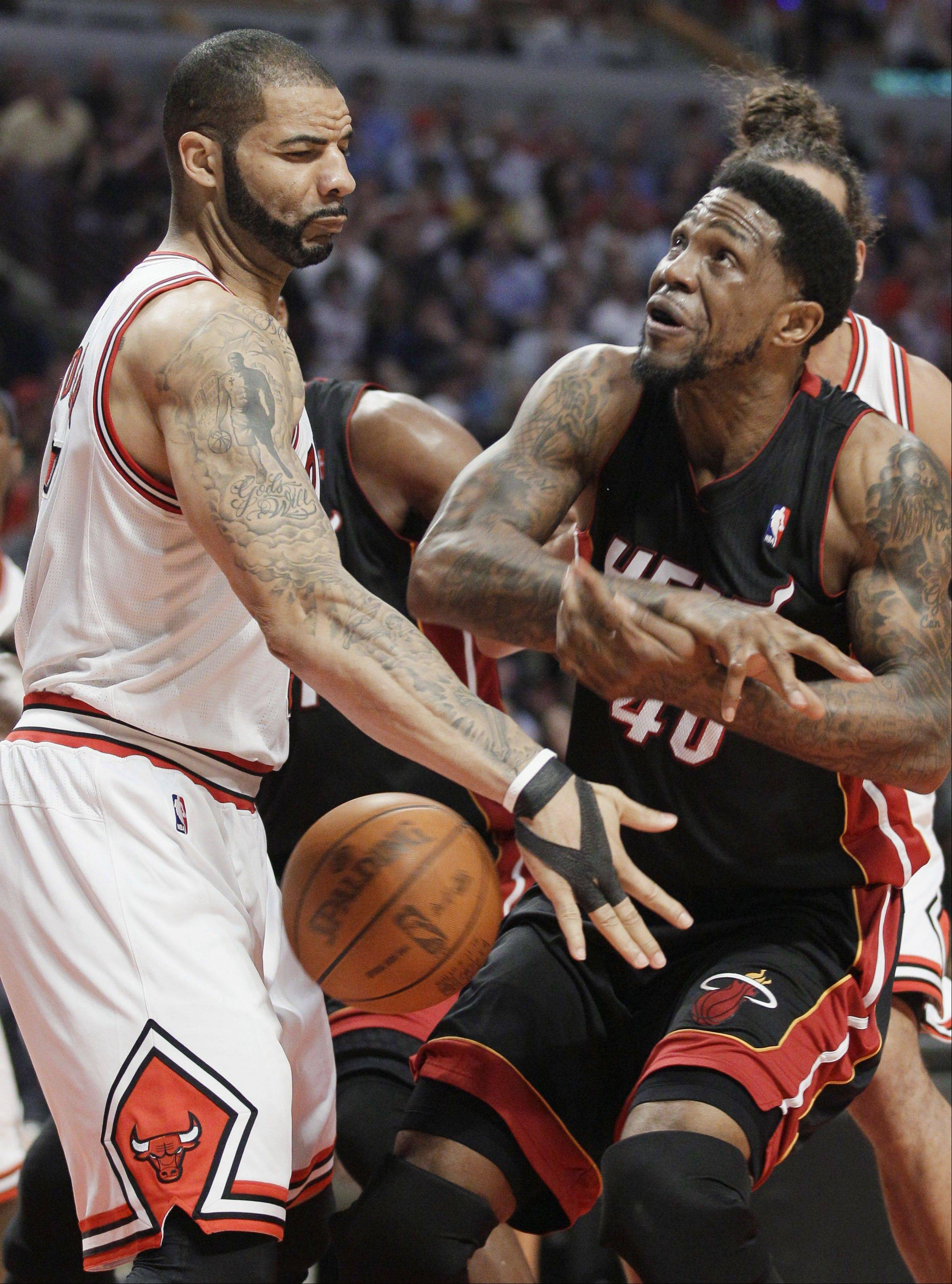 Bulls forward Carlos Boozer (5) steals the ball from Miami Heat forward Udonis Haslem (40) during the first half of an NBA basketball game in Chicago, Wednesday, March 14, 2012.