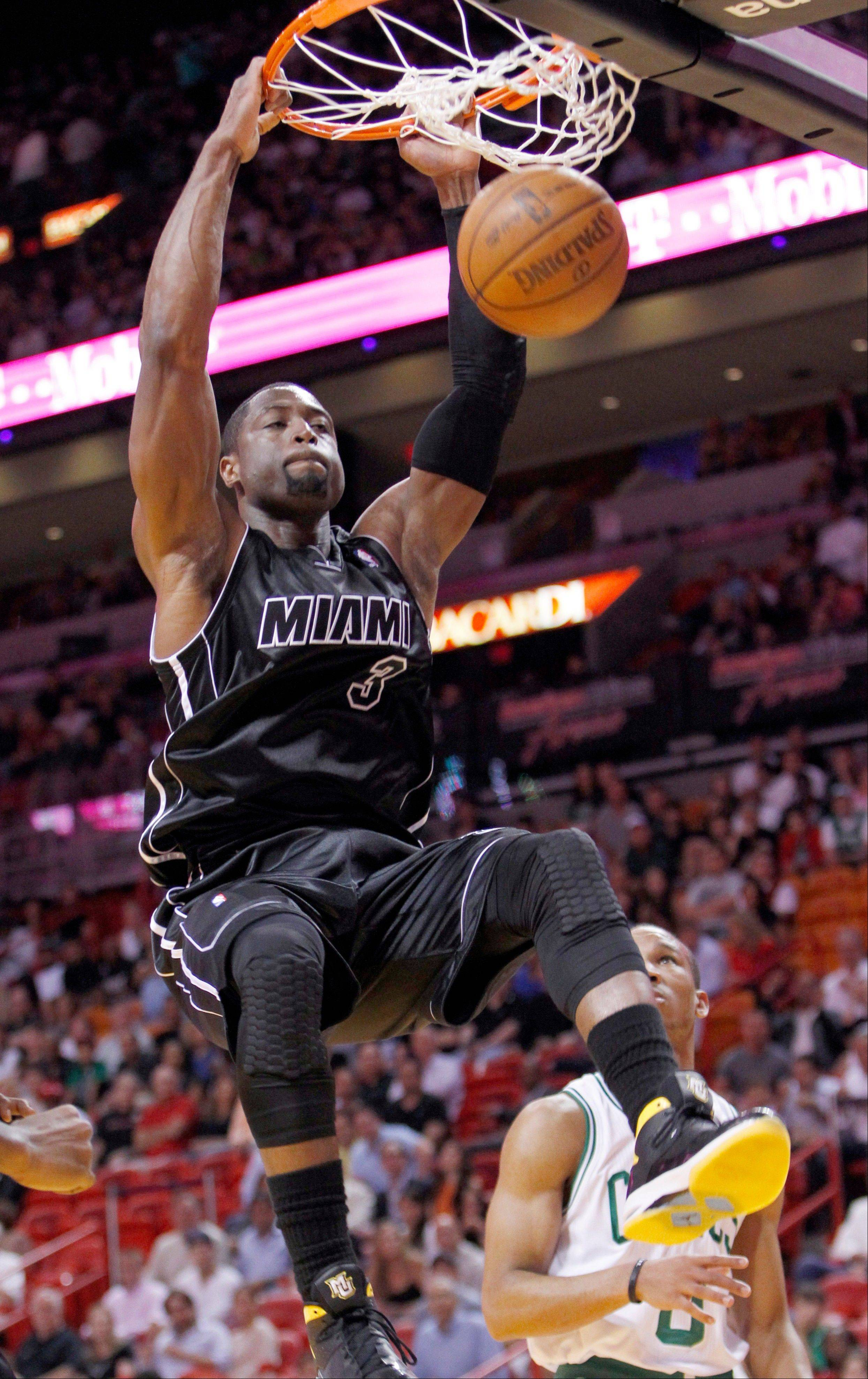 Miami Heat guard Dwyane Wade (3) dunks the ball as Boston Celtics guard Avery Bradley, rear, looks on during the first half of an NBA basketball game, Tuesday, April 10, 2012 in Miami.