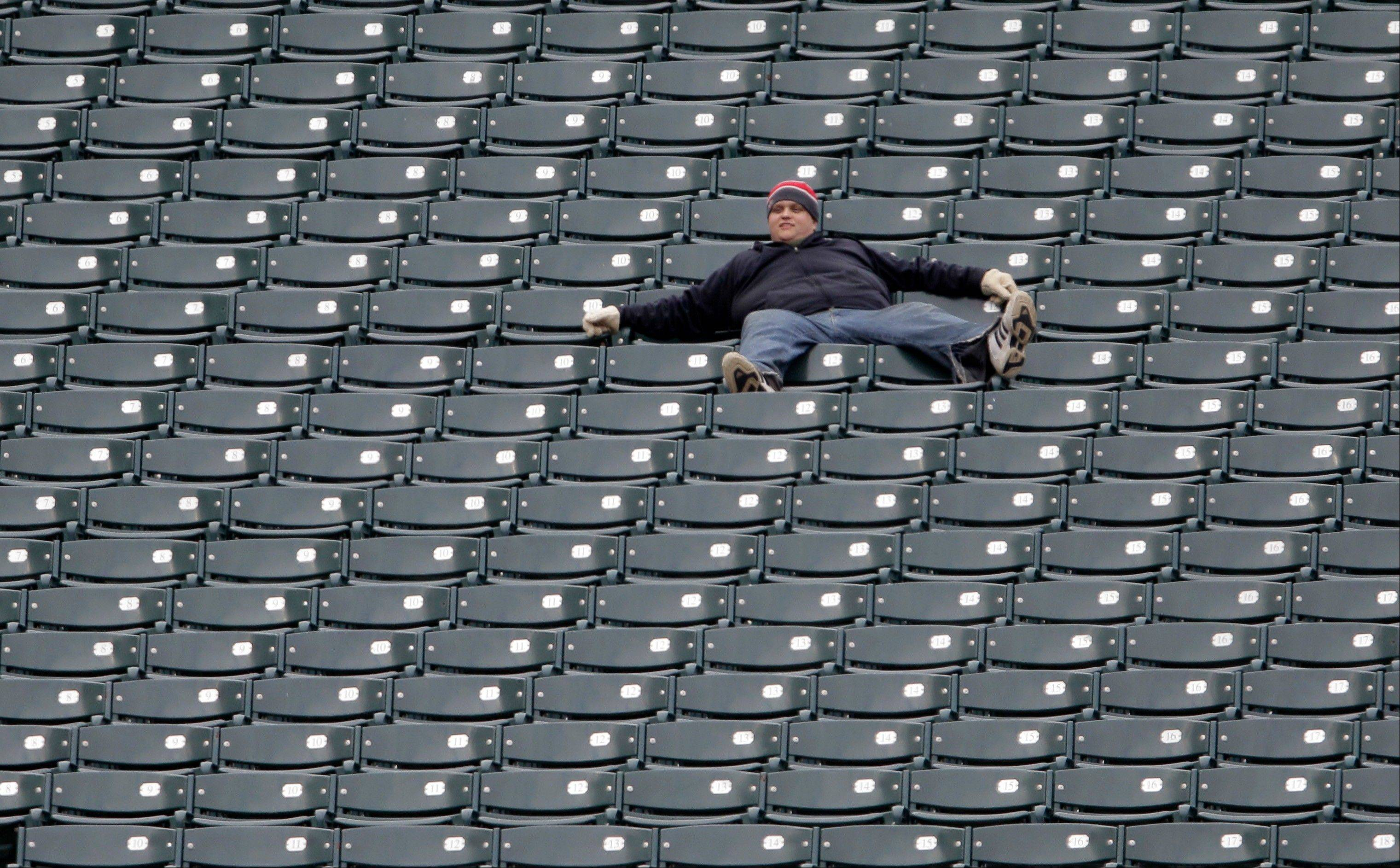 A Cleveland Indians fan watches alone from the left field stands in the ninth inning of the Indians 10-6 loss to the Chicago White Sox in a baseball game in Cleveland on Wednesday, April 11, 2012.