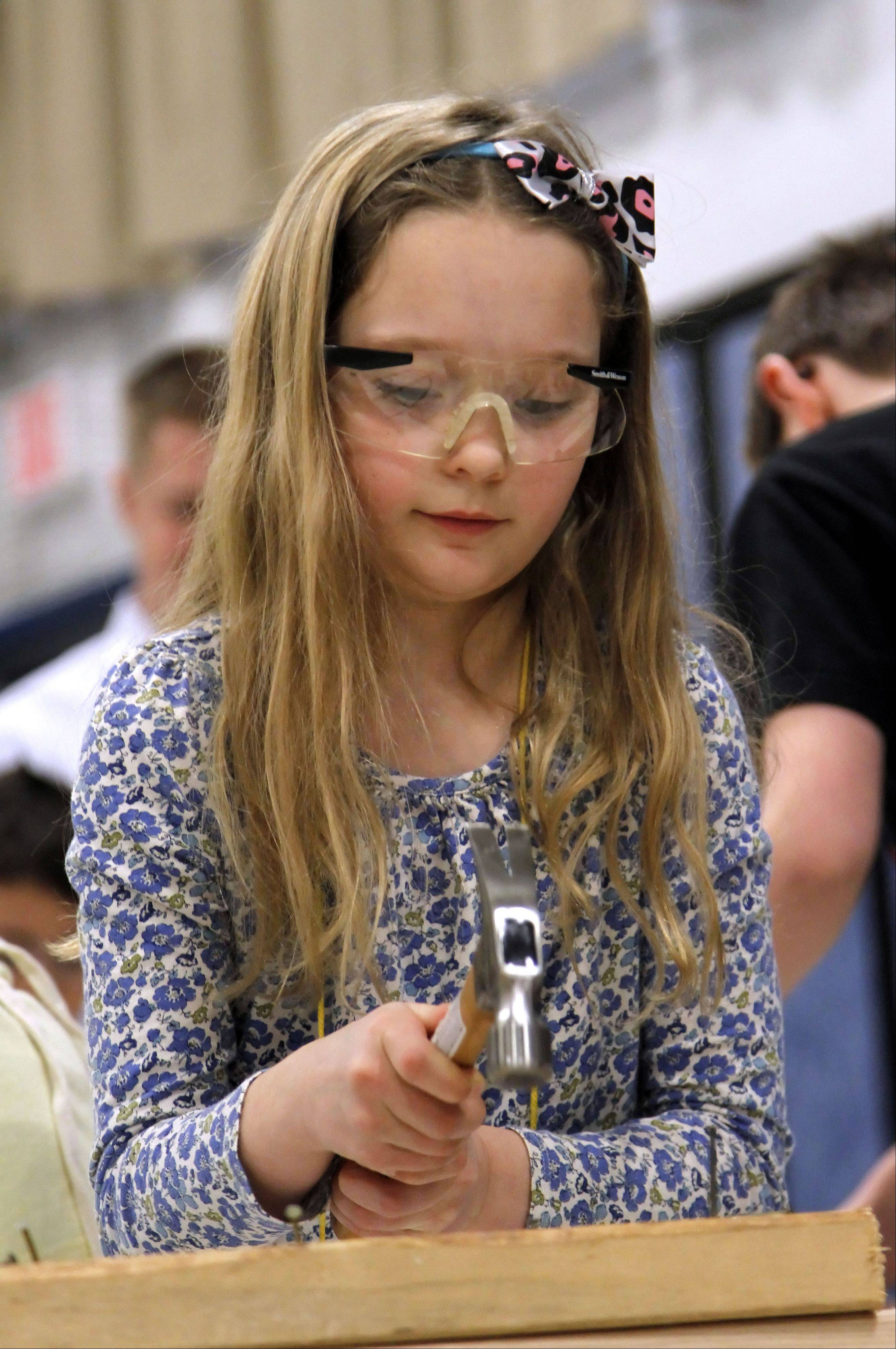 Emaline Frey, 7, gets the opportunity to pound some nails during career day at Rockland School in Libertyville.