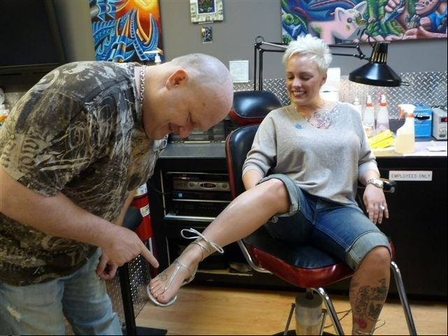 Pointing out one of three autism tattoos sported by Sara Allgire, Jaime Ozman met his wife at Rising Phoenix Tattoo in Addison. The couple, who own the studio, are hosting an autism fundraiser this weekend.