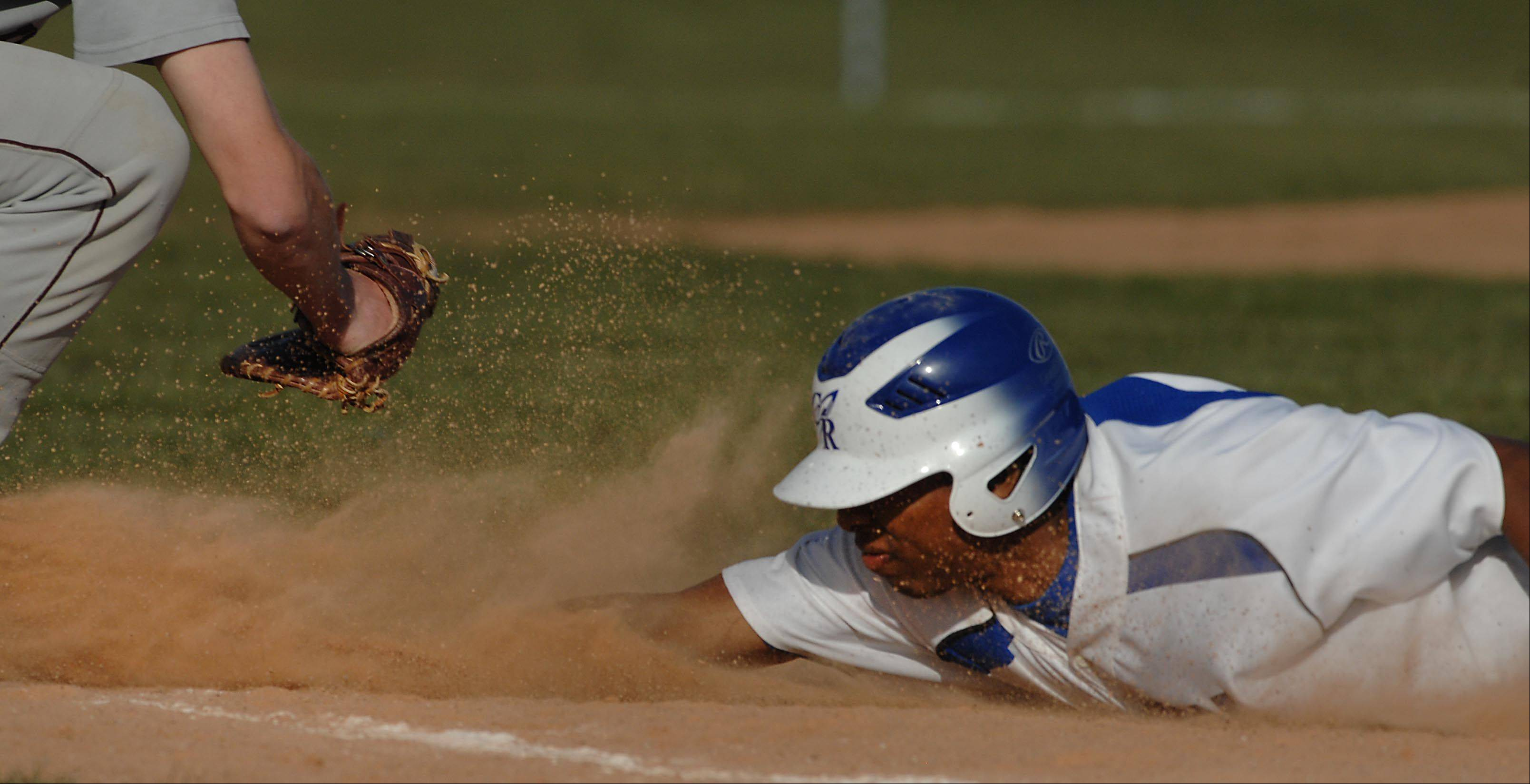 Burlington Central's Ray Hunnicutt dives safely back to first base before the throw from Marengo's Bobby Shute Thursday in Burlington. Hunnicutt later scored.