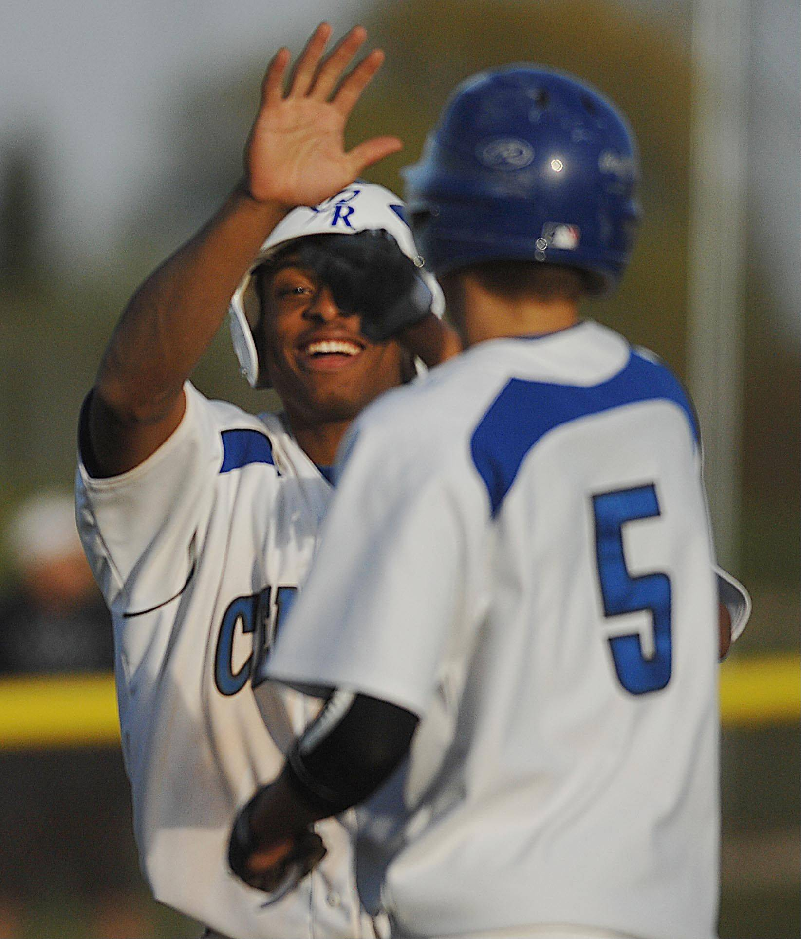 Burlington Central's Ray Hunnicutt congratulates teammate Michael Scott on his game-winning RBI base hit to make the score 10-0 over Marengo Thursday in Burlington.