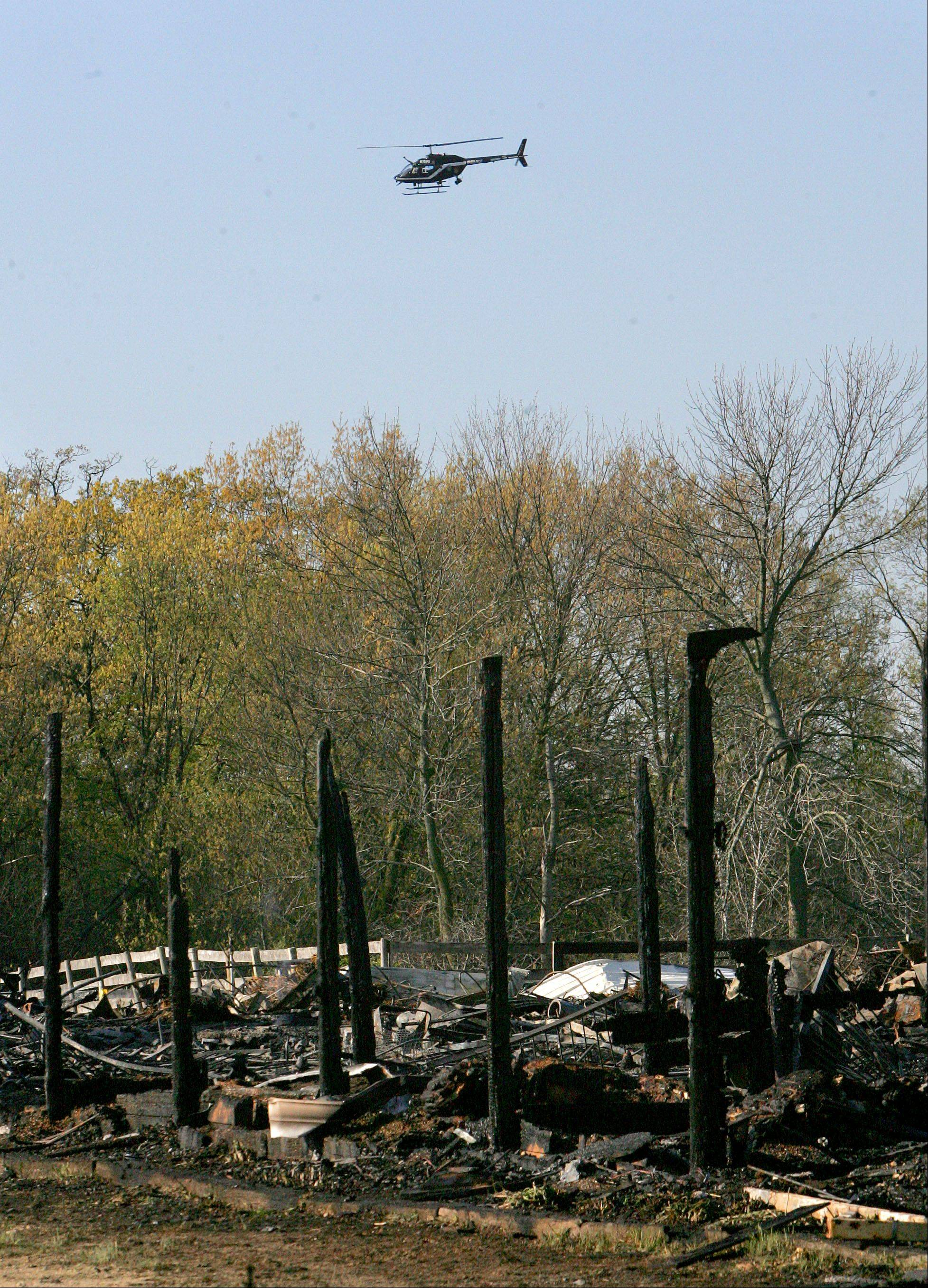 Police helicopters search the area around Black Tie Stable for missing horses Thursday morning, a day after a fire destroyed the facility and killed at least 18 horses in McHenry County.