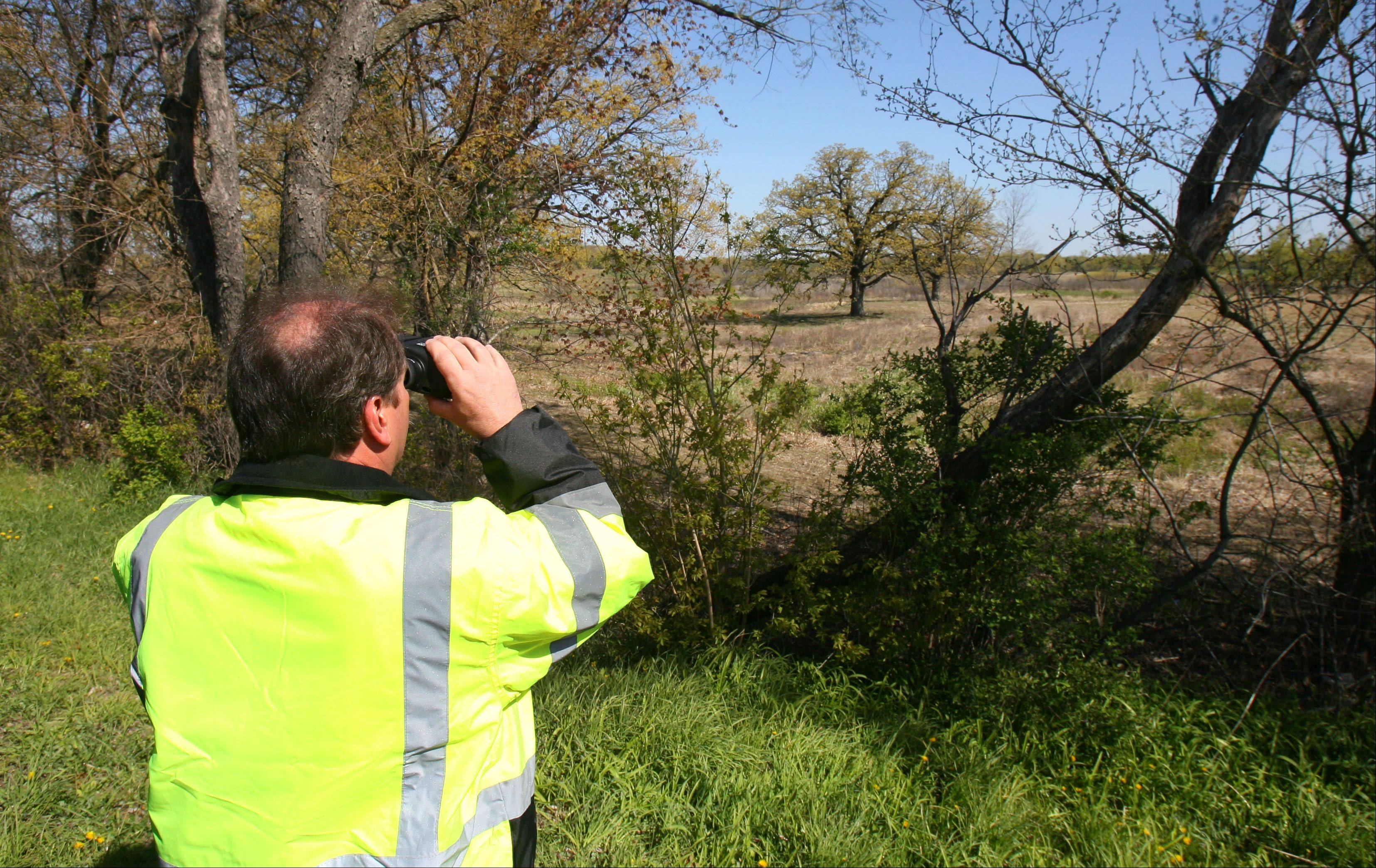 Brent Deppmeier, a volunteer and helicopter pilot from Air One Emergency Response, uses binoculars to survey an open area west of Volo Bog during a search for horses that escaped Wednesday's fire at Black Ties Stable in McHenry County.