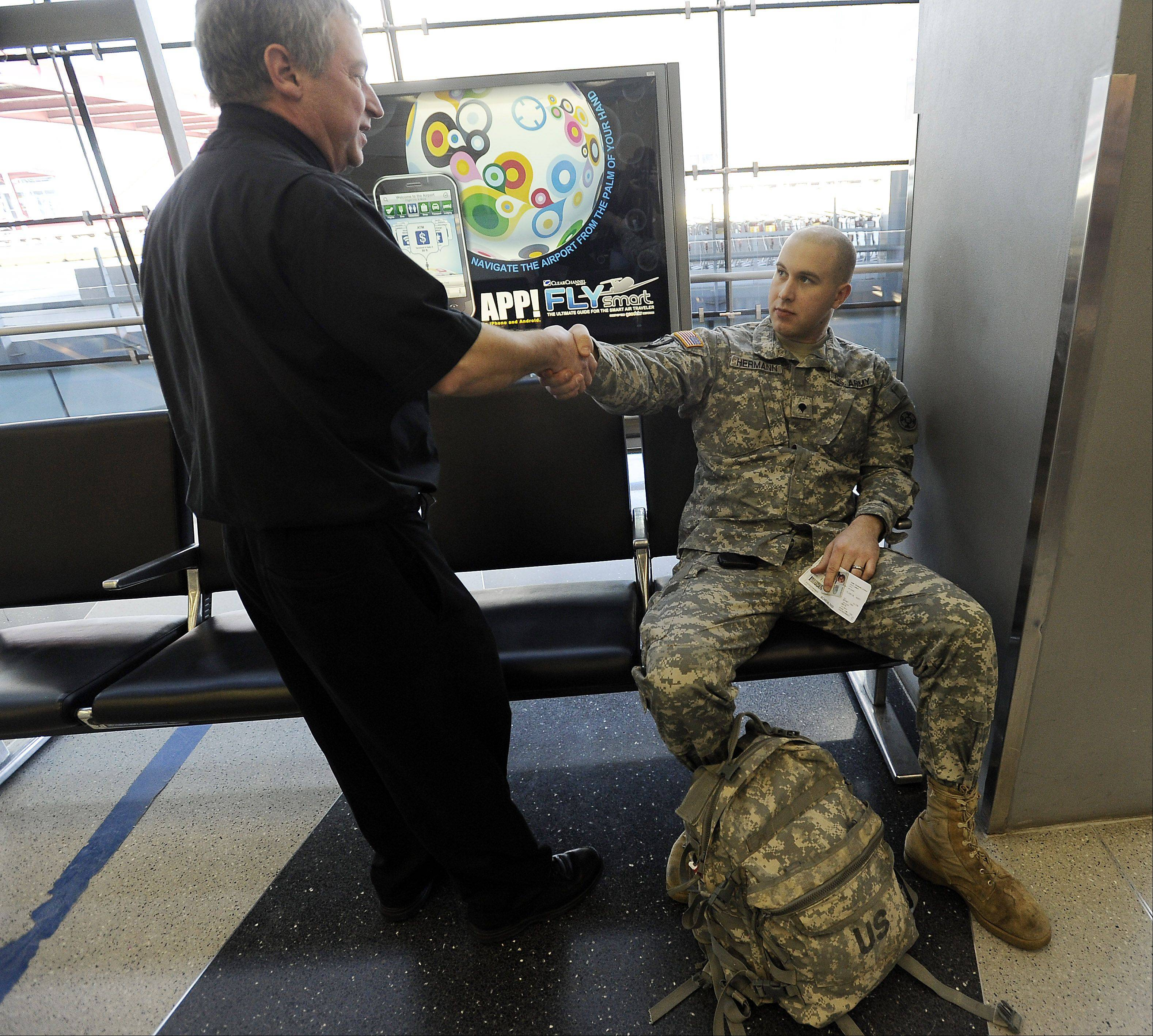 Father Mike, as he is known at O'Hare International Airport, walks Terminal 2 outside the airport's Interfaith Chapel, listening to travelers such as this soldier heading down south for training.