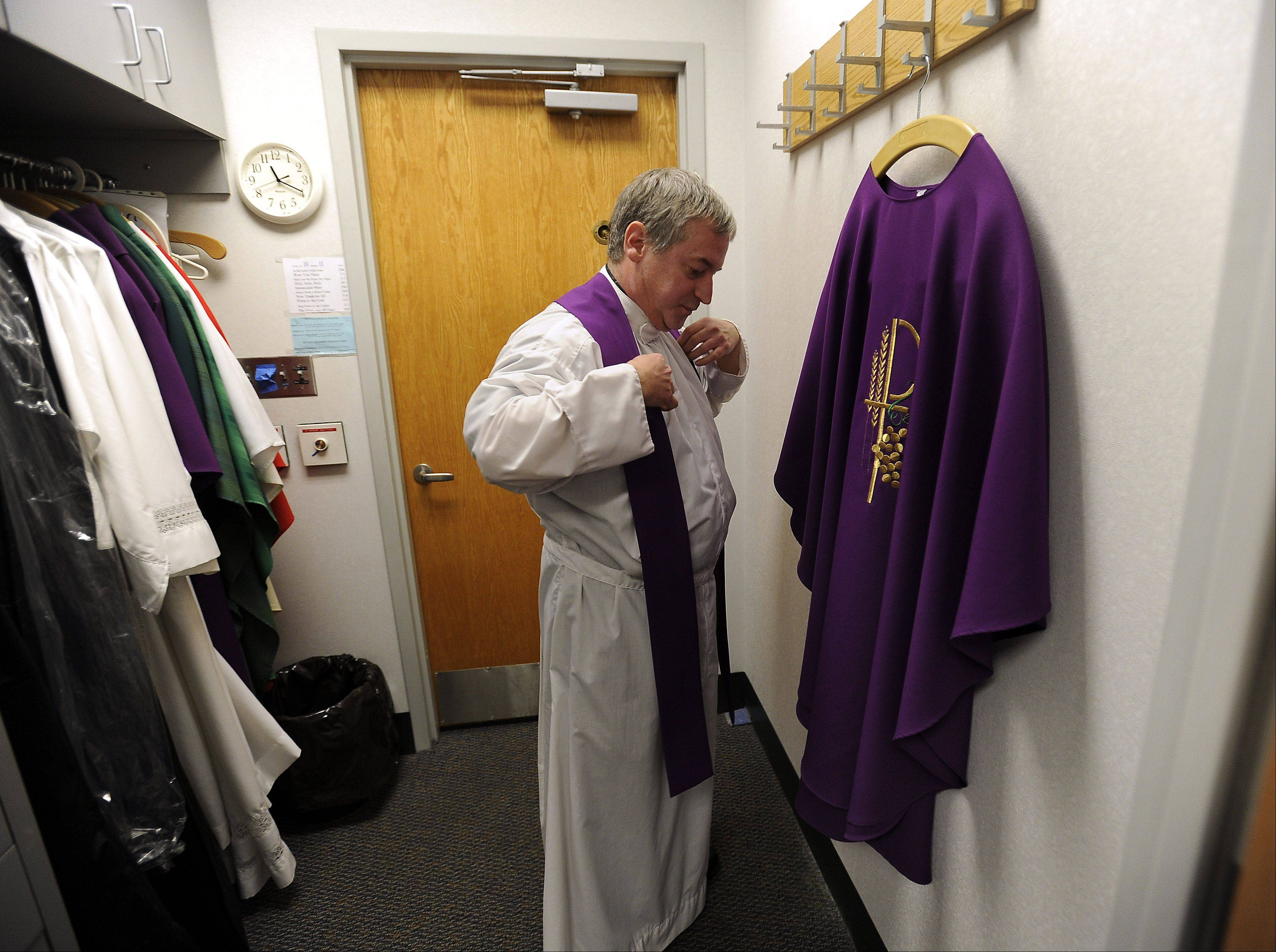 Father Mike prepares himself for Mass by donning his vestments.