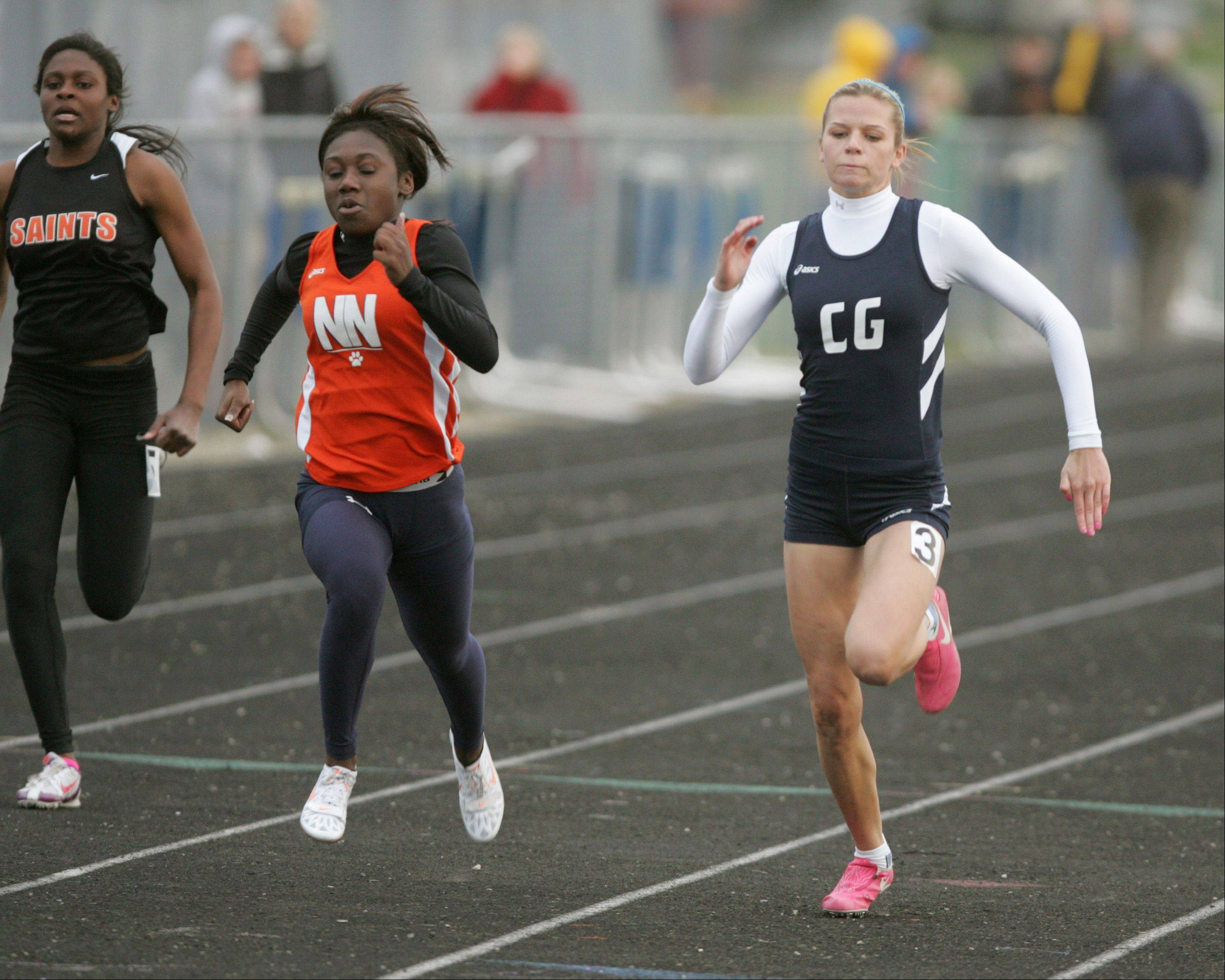 "St Charles East's Britney Williams, Naperville North's Alexis Hyshaw, and Cary Grove's Sarah Ryan run the Girls 100 Meter Dash, during the ""Gus Scott Classic"" Boys and Girls Track Invitational at Naperville North High School."