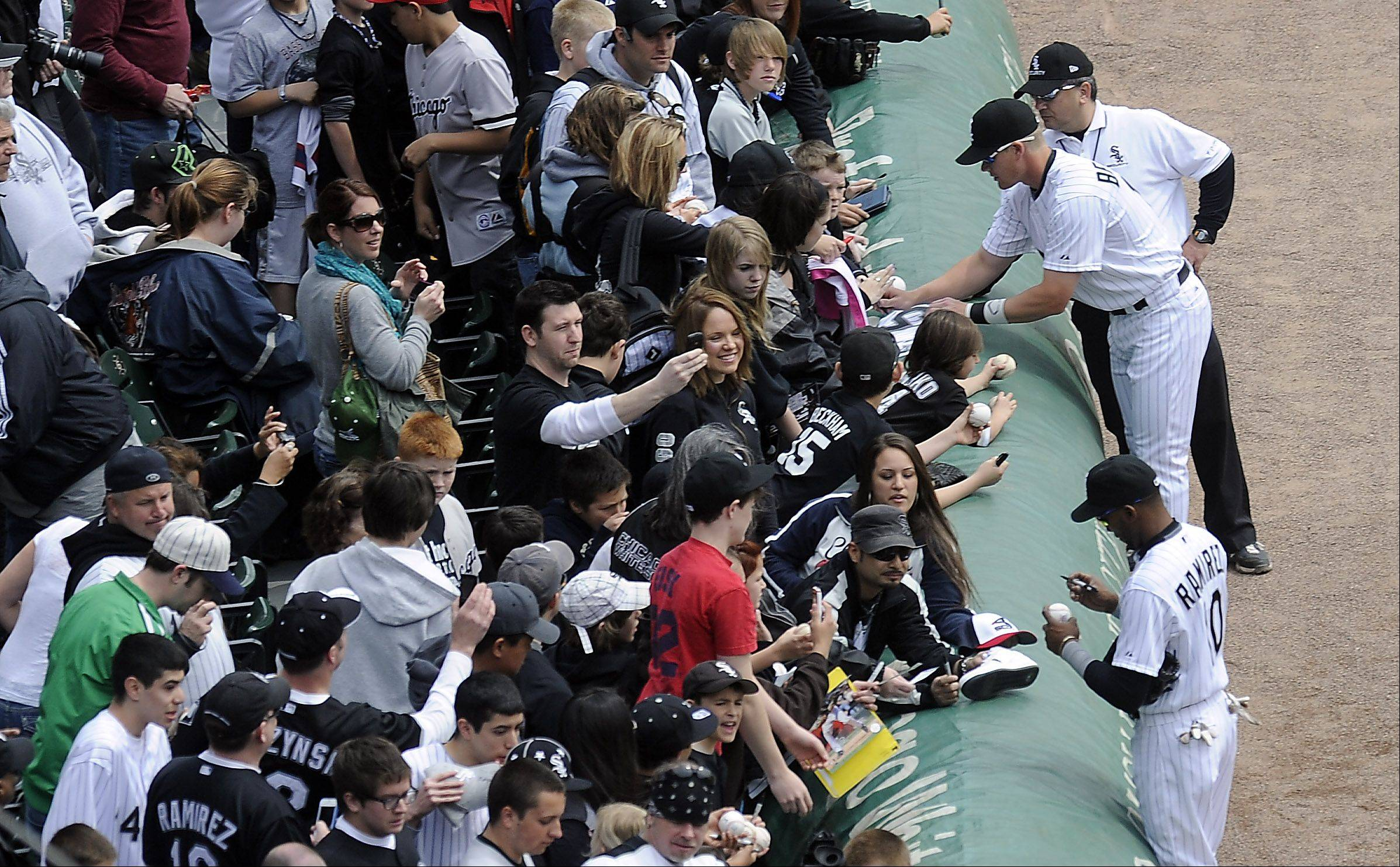 White Sox players sign autographs for the fans before the game.