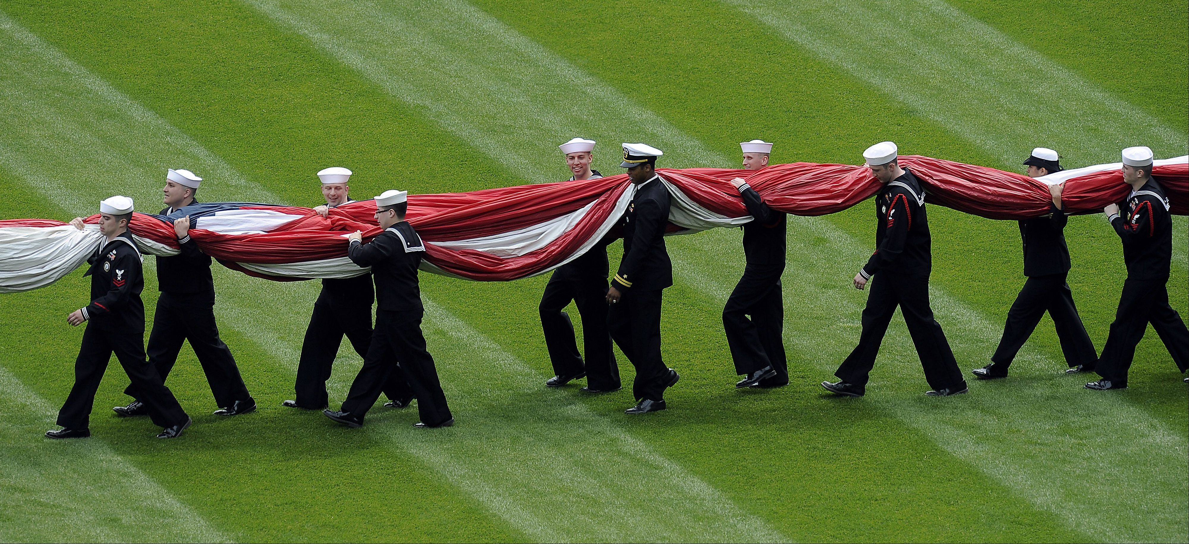 Military personnel carry out a giant flag which was displayed for the National Anthem.