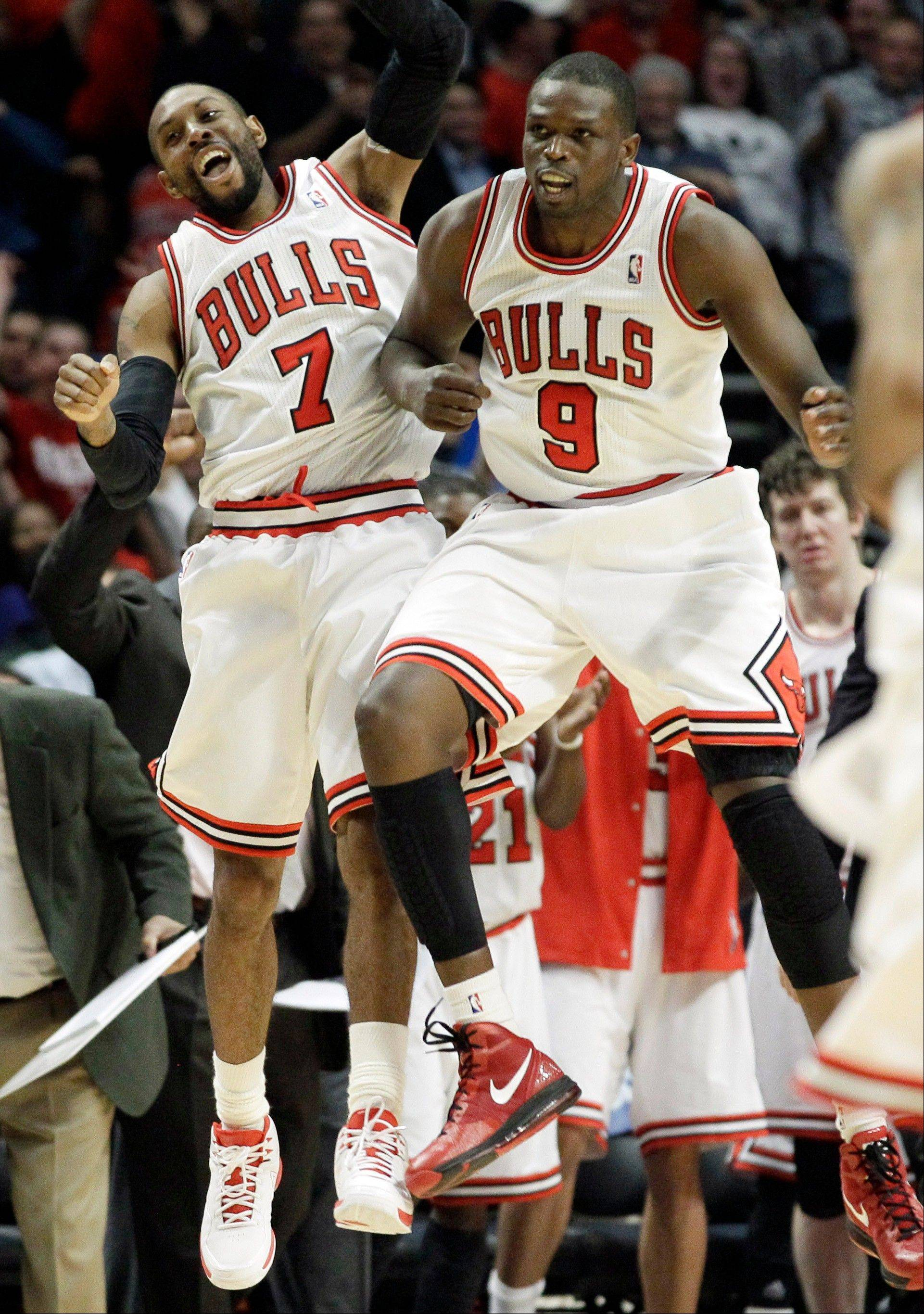 Bulls guard C.J. Watson (7) celebrates with forward Luol Deng (9) after Watson scored a 3-point basket during the second half Thursday night.