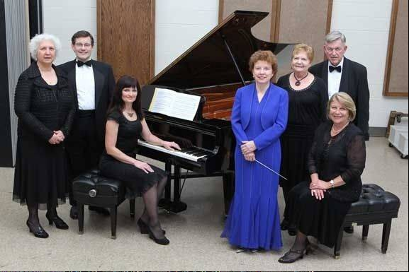 The Oakton Six Piano Ensemble consists of, from left, Marianne Pyster, Chicago; Garfield Sallman, Des Plaines; Viktoriya Gordiyenko, Morton Grove; Glenna Sprague, conductor, Skokie; Beatriz Levi, sitting on bench, Northfield; Lina Schaal, Chicago; Manigirdas Motekaitis, Chicago.