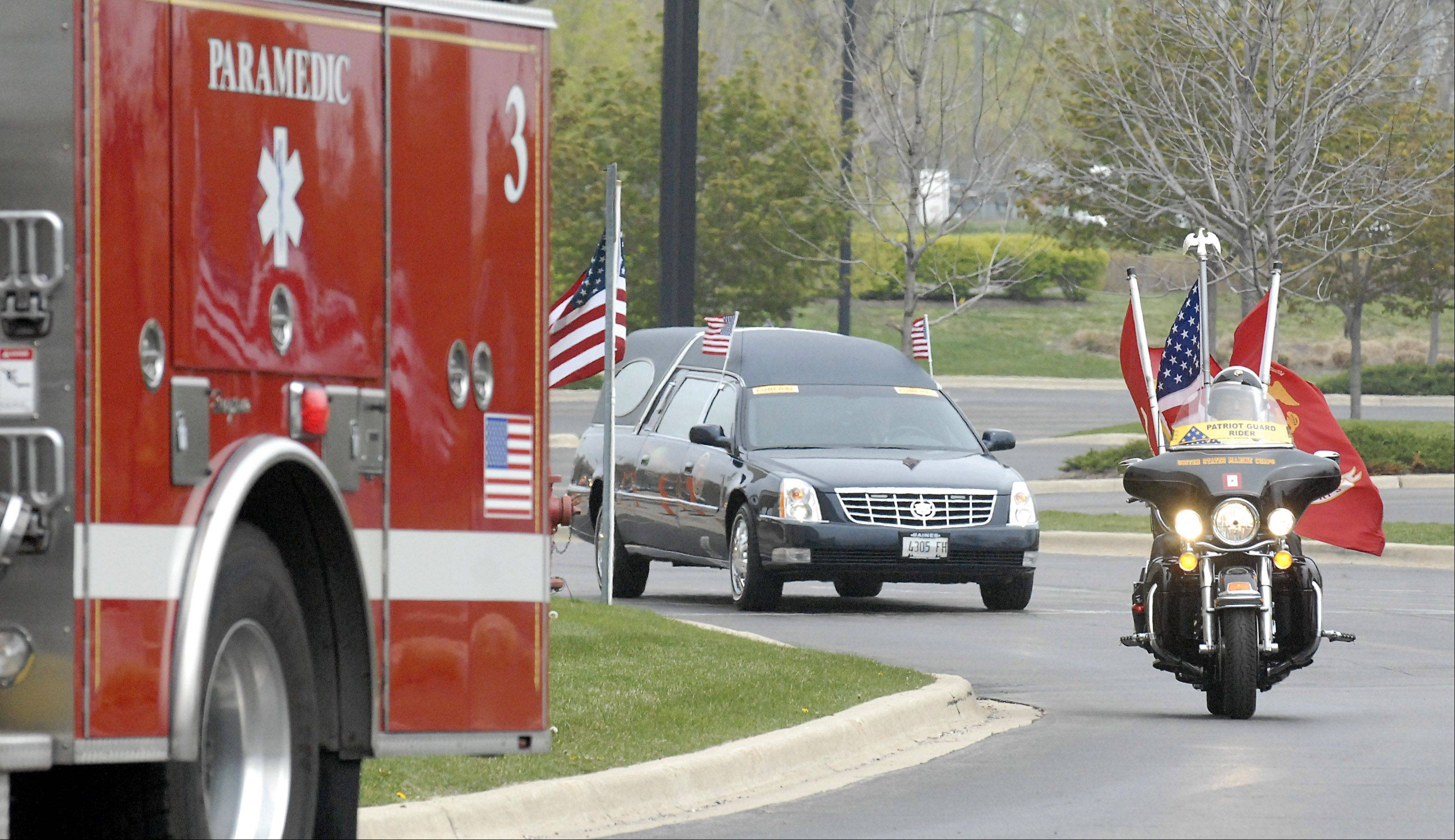 Firetrucks, ambulances and Patriot Guard riders escort the hearse of Cpl. Alex Martinez to Life Changers International Church in Hoffman Estates on Saturday. The Marine from Elgin was killed during combat operations in Afghanistan.