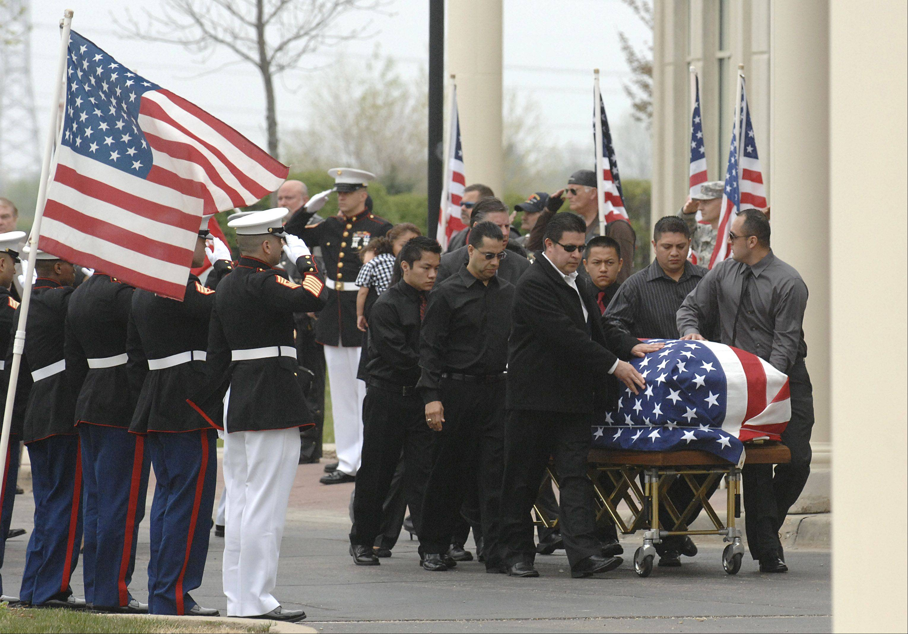The casket of Cpl. Alex Martinez is escorted into Life Changers International Church for his funeral in Hoffman Estates on Saturday. The Marine from Elgin was killed during combat operations in Afghanistan.