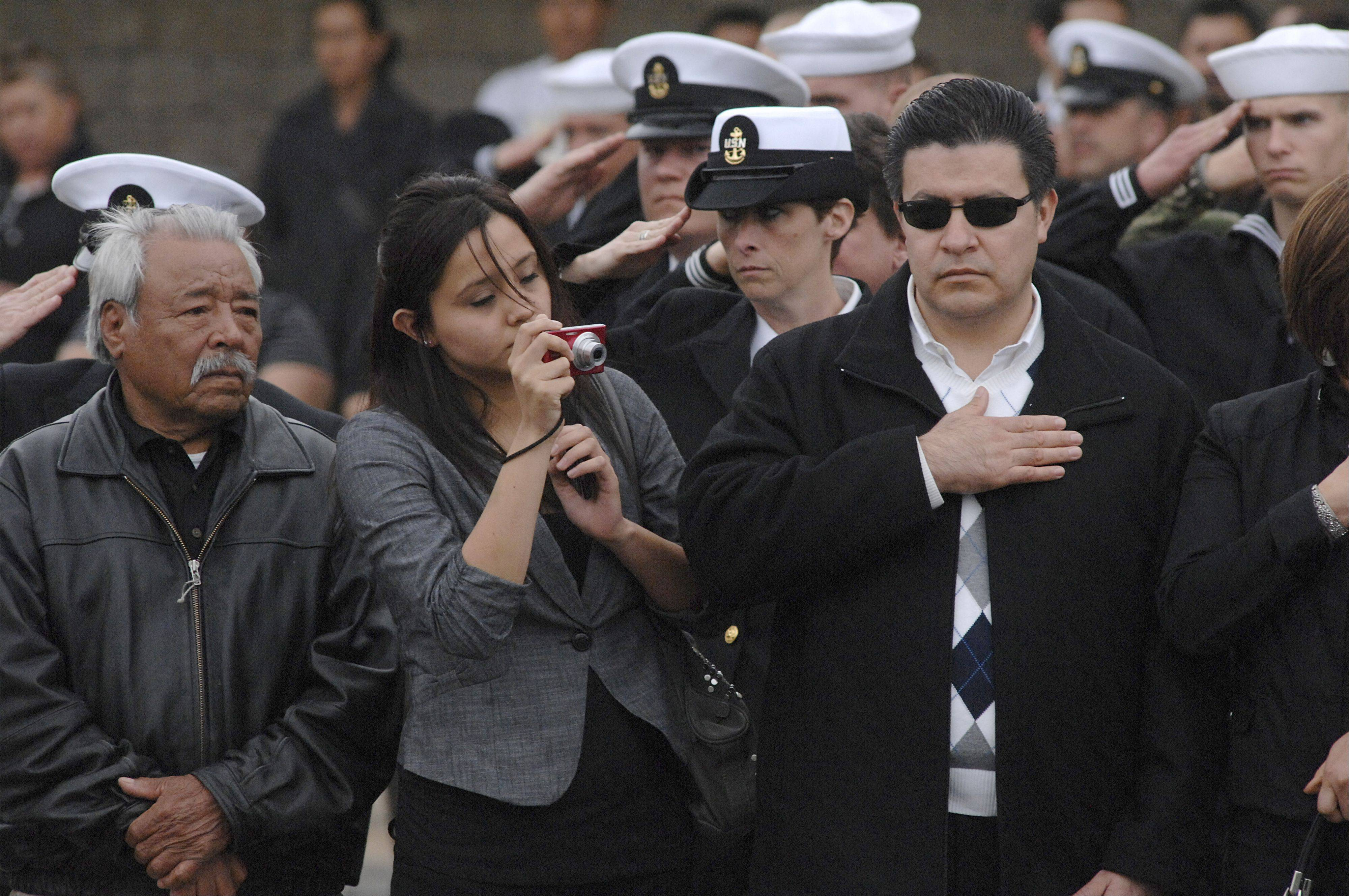 Members of the military, family and friends of Cpl. Alex Martinez salute or place their hands over their hearts as the limos carrying his wife, Julianna, and immediate family away Saturday after his funeral at Life Changers International Church in Hoffman Estates.