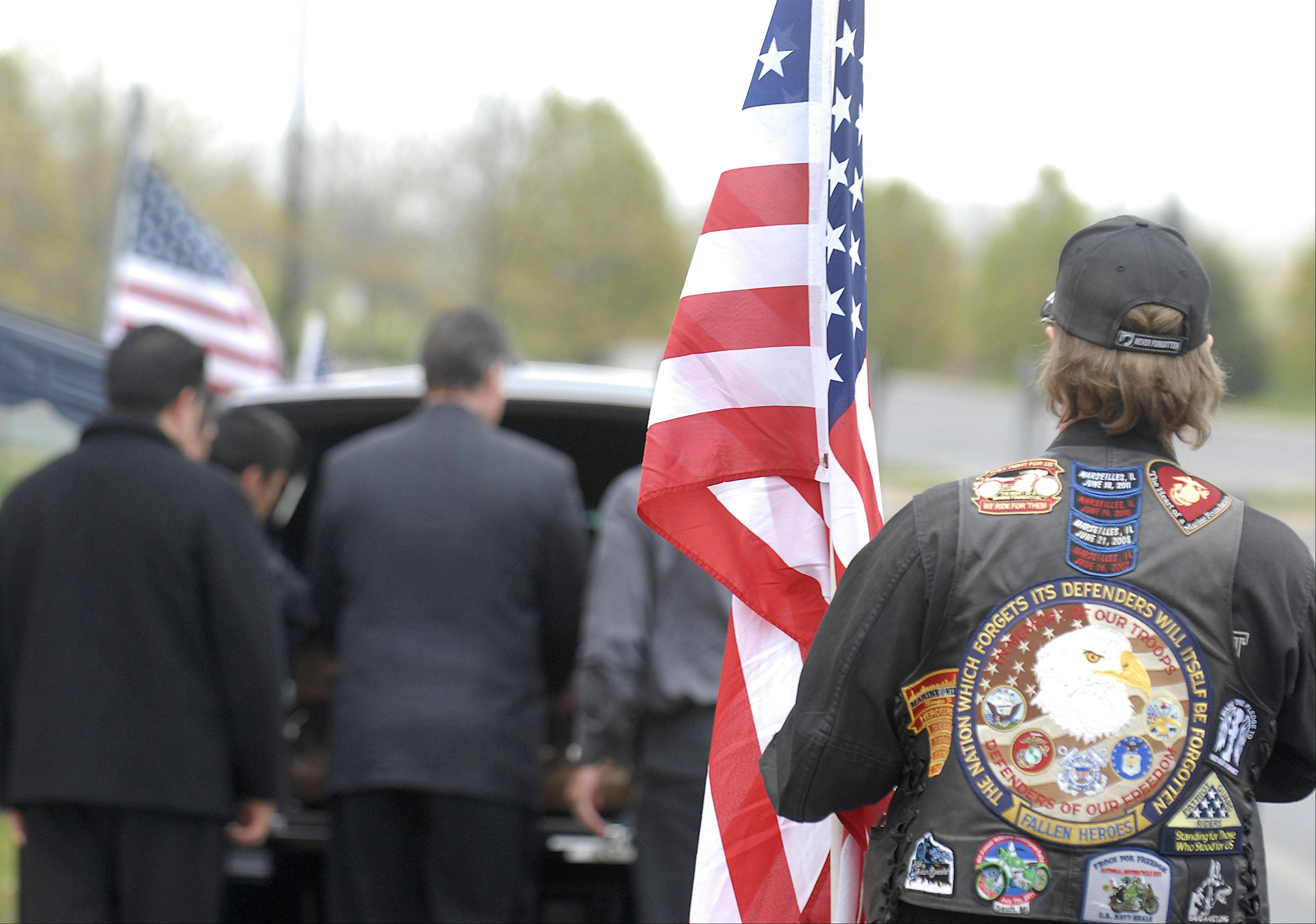 A member of the Patriot Guard stands at attention as the casket of Cpl. Alex Martinez is loaded into the hearse after his funeral on Saturday.