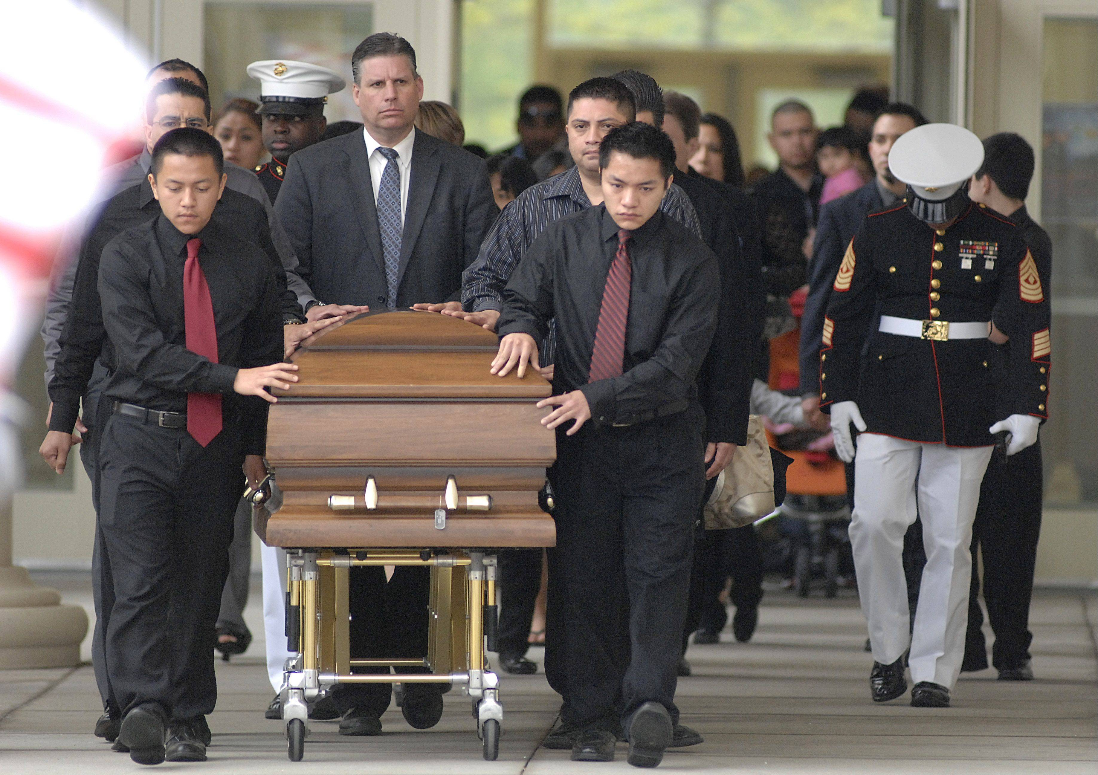 The casket of Cpl. Alex Martinez is escorted out of Life Changers International Church in Hoffman Estates after his funeral on Saturday. The Marine from Elgin was killed during combat operations in Afghanistan.