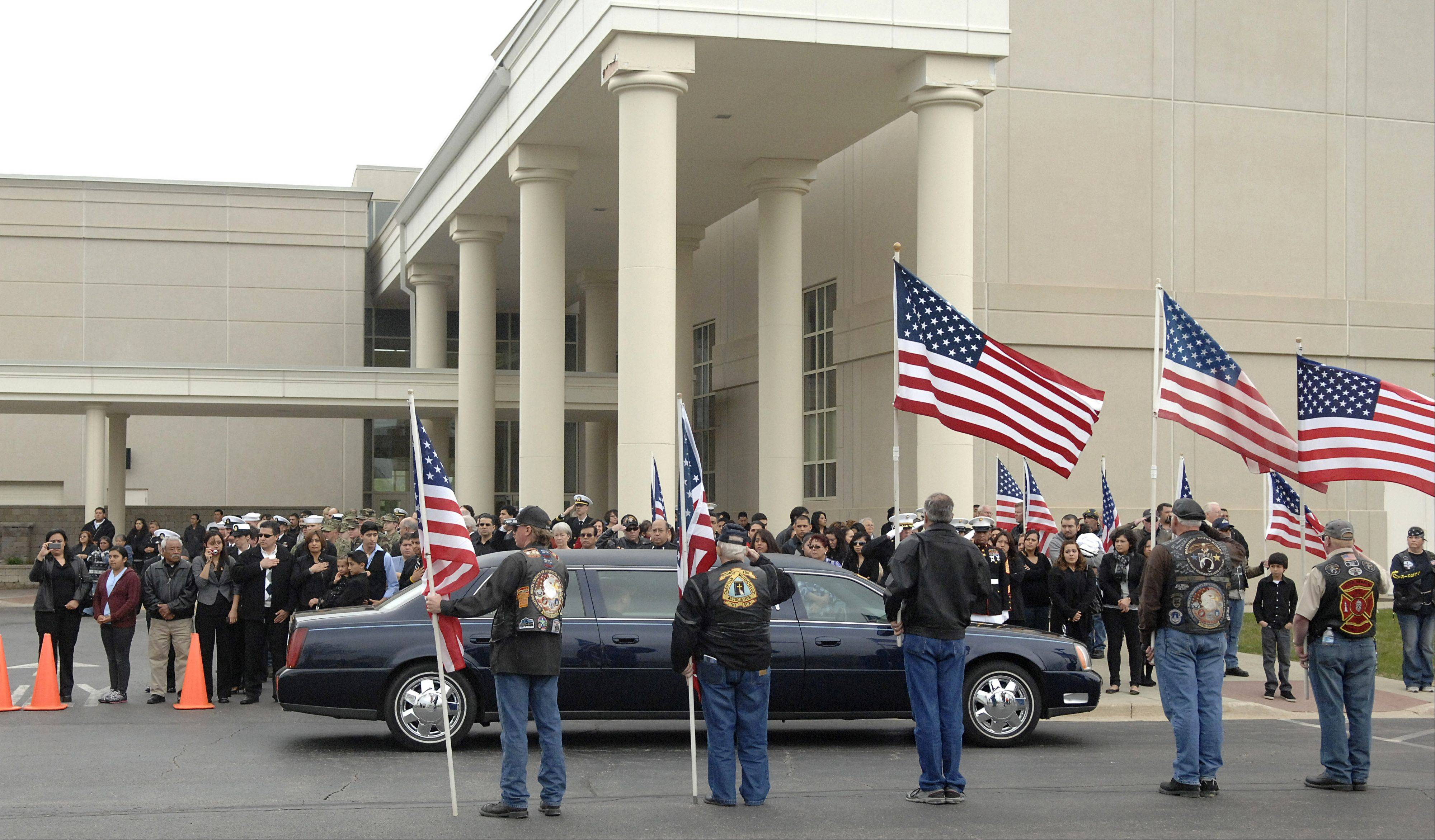 Members of the military, family and friends of Cpl. Alex Martinez salute or place their hands over their hearts as limousines carrying his wife, Julianna, and immediate family drive away following his funeral Saturday at Life Changers International Church in Hoffman Estates.