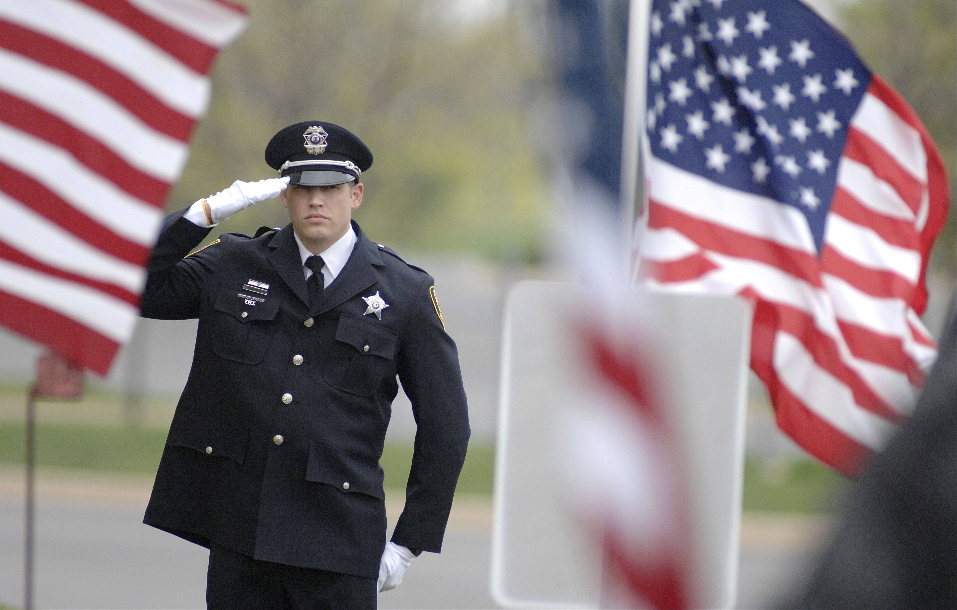 An Elgin police officer stands at attention as the casket of Cpl. Alex Martinez is loaded into the hearse Saturday after his funeral.