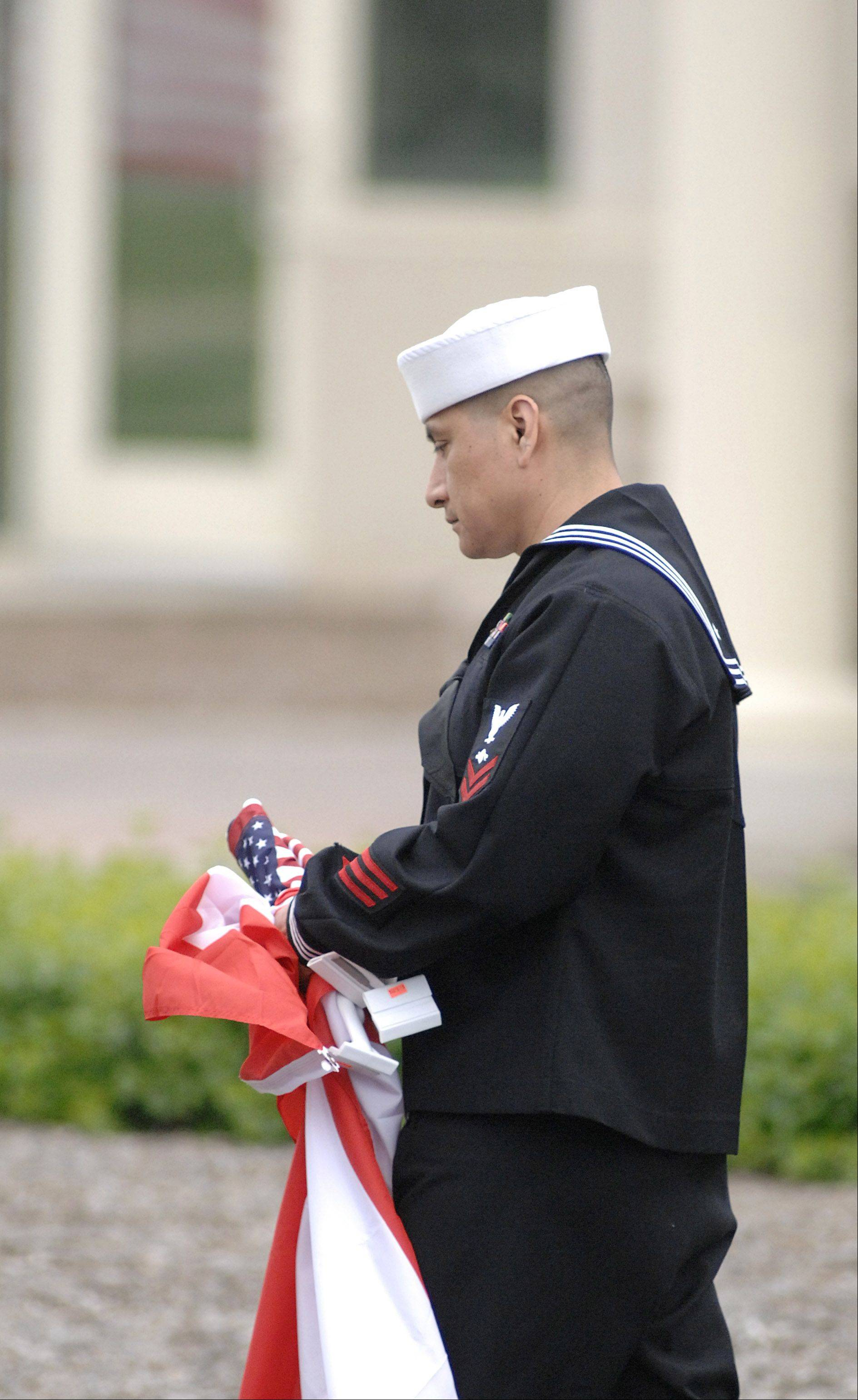 Enrique Martinez of Huntley, father of the late Cpl. Alex Martinez, leaves Life Changers International Church in Hoffman Estates after being presented with flags by a VFW member on Saturday.