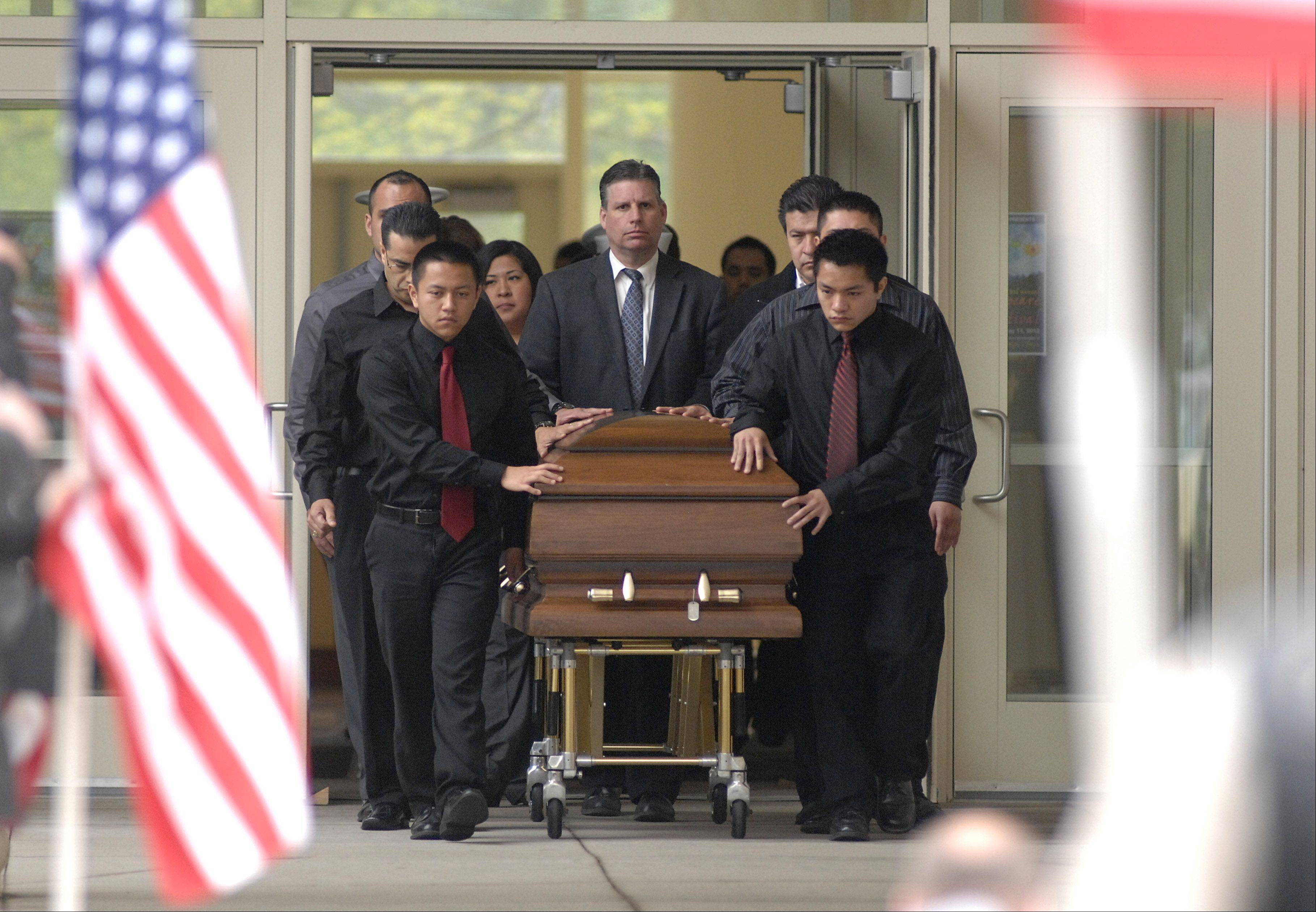 The casket of Cpl. Alex Martinez is escorted out of Life Changers International Church, with widow Julianna Martinez following, after his funeral in Hoffman Estates on Saturday. The Marine from Elgin was killed during combat operations in Afghanistan.