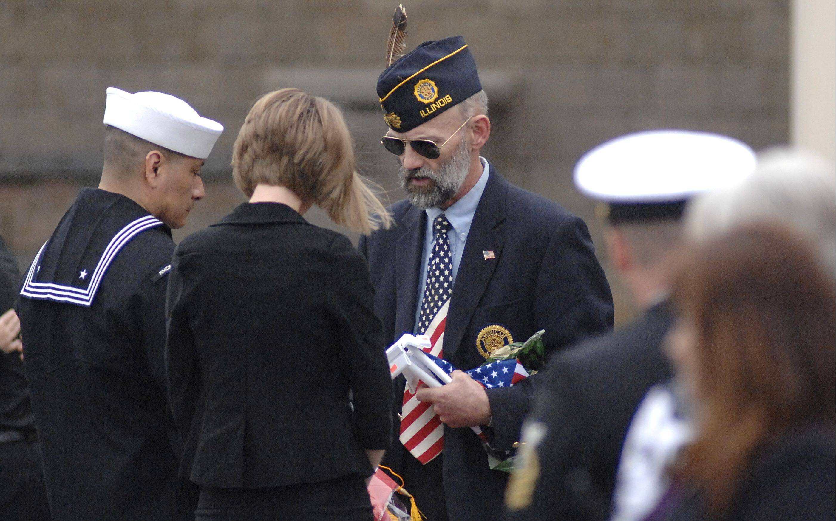 Enrique Martinez of Huntley, father of the late Cpl. Alex Martinez, is presented with flags and the golden star by a VFW member after Martinez's funeral on Saturday.