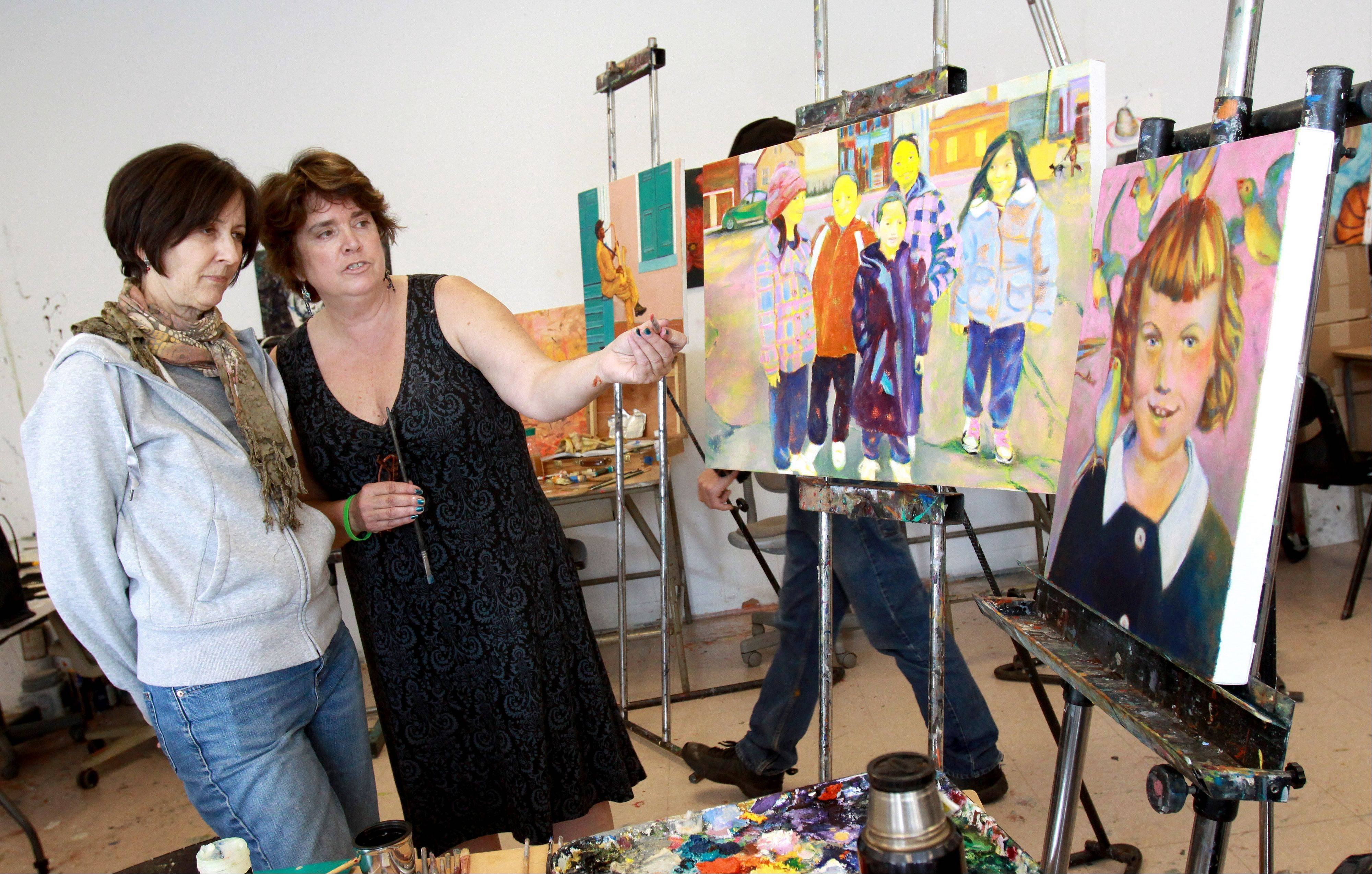 Art professor Jennifer Hereth, right, helps Antoinette Traynor of Naperville with her paintings. COD students are doing 36 portraits representative of children who attended Maternity B.V.M. during its 100 years in Chicago's Humboldt Park neighborhood.