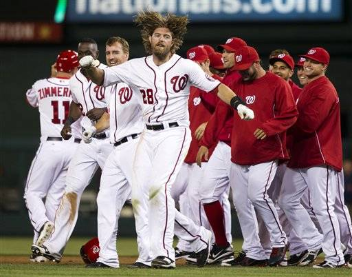 Washington Nationals right fielder Jayson Werth escapes from his teammates after being rushed for hitting the game-winning single during the 13th inning of a baseball game against the Cincinnati Reds on Friday, April 13.