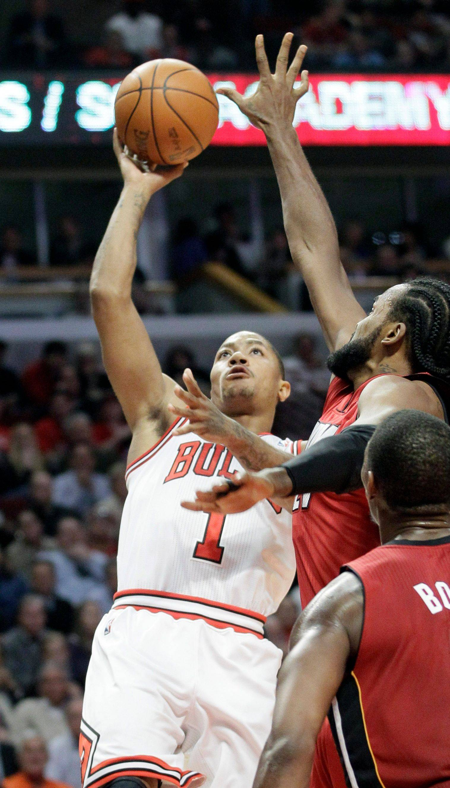 Bothered by a sprained ankle, the Bulls' Derrick Rose, left, scored just 2 points Thursday on 1-of-13 shooting against the Heat at the United Center.