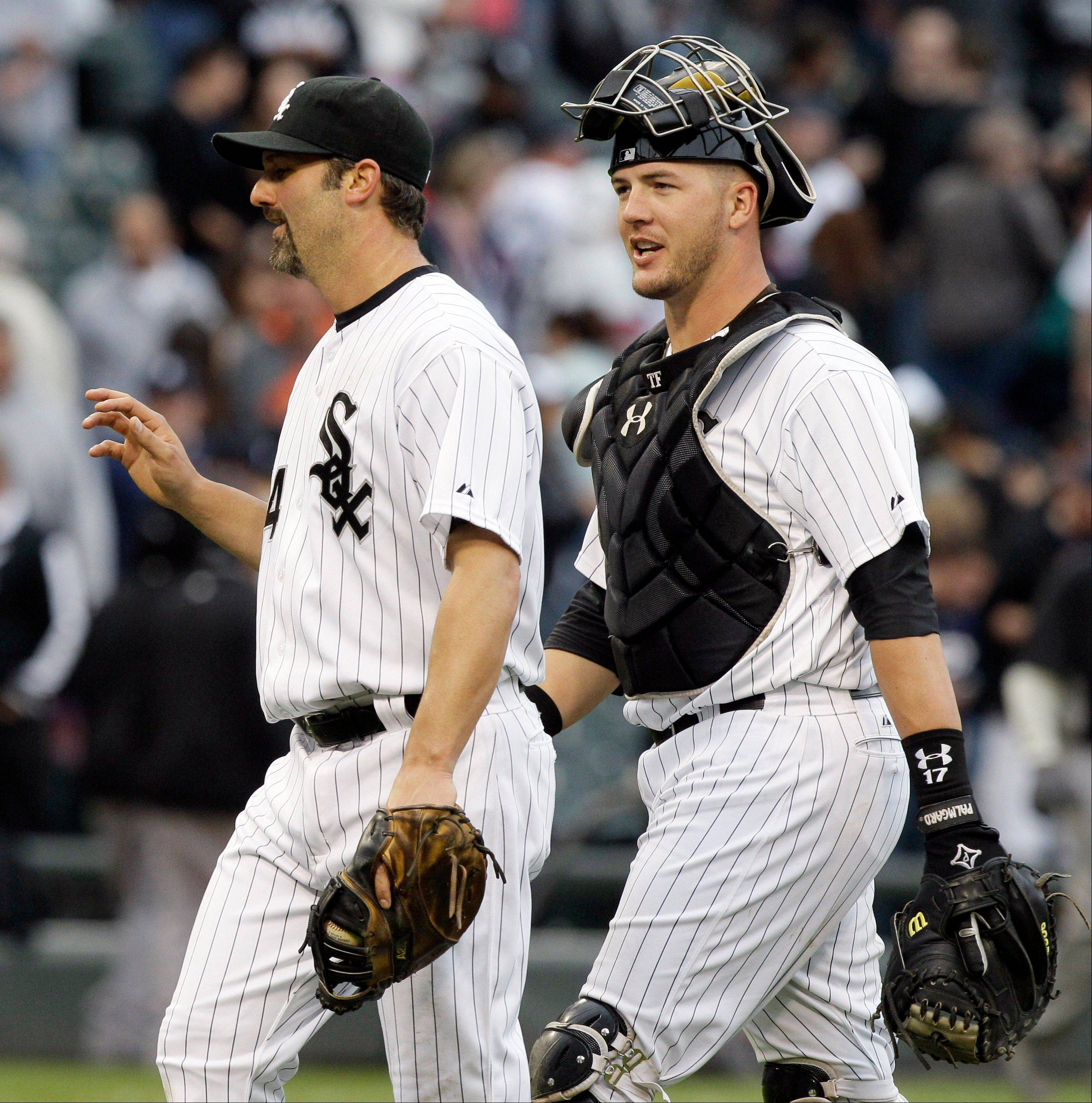 Chicago White Sox catcher Tyler Flowers, right, smiles as he talks to Paul Konerko after the White Sox defeated the Detroit Tigers 5-1 in a baseball game in Chicago, Saturday, April 14, 2012.