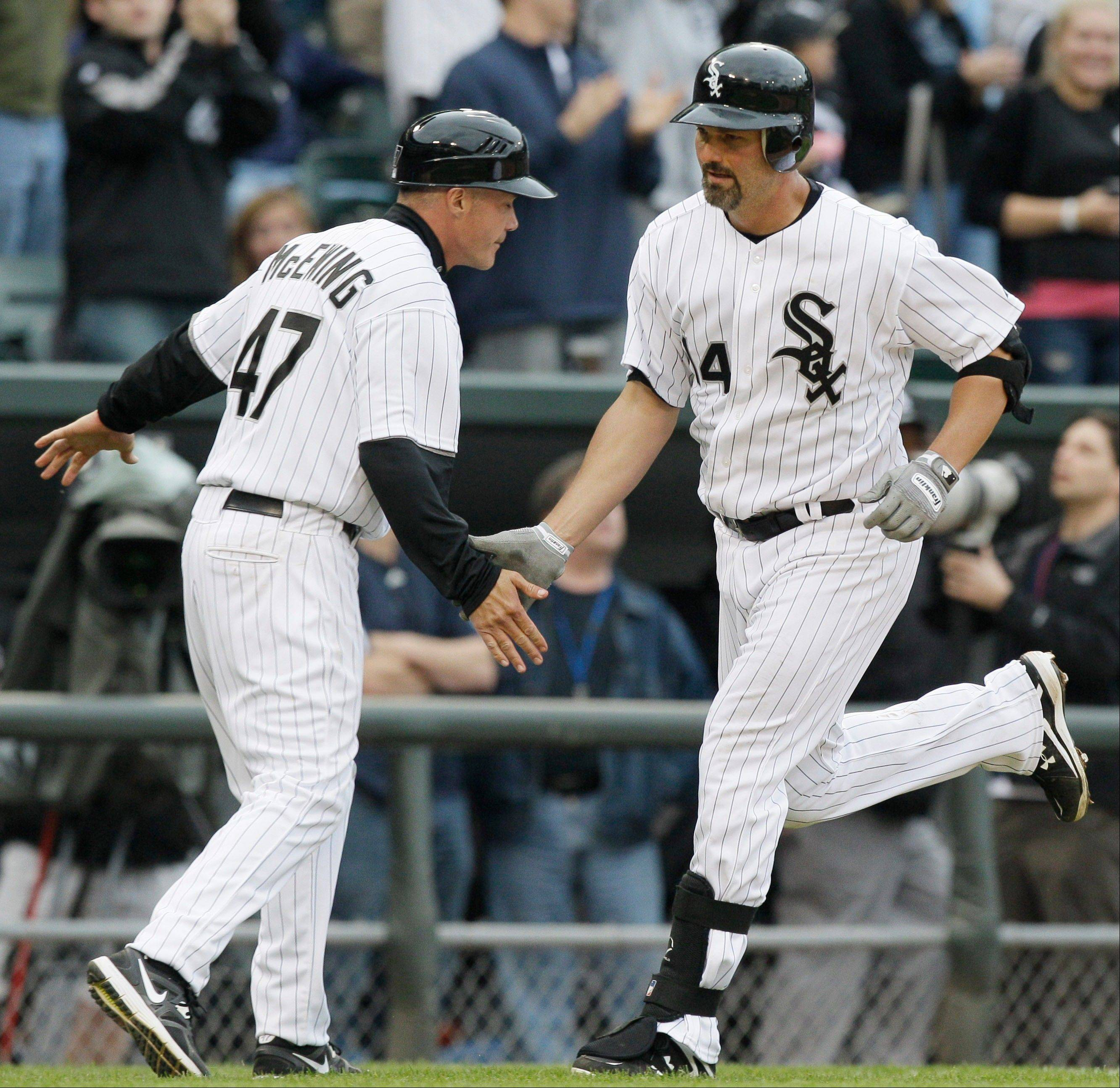 Chicago White Sox's Paul Konerko, right, celebrates with third base coach Joe McEwing after hitting a solo home run during the eighth inning of a baseball game against the Detroit Tigers in Chicago, Saturday, April 14, 2012. The White Sox won 5-1.