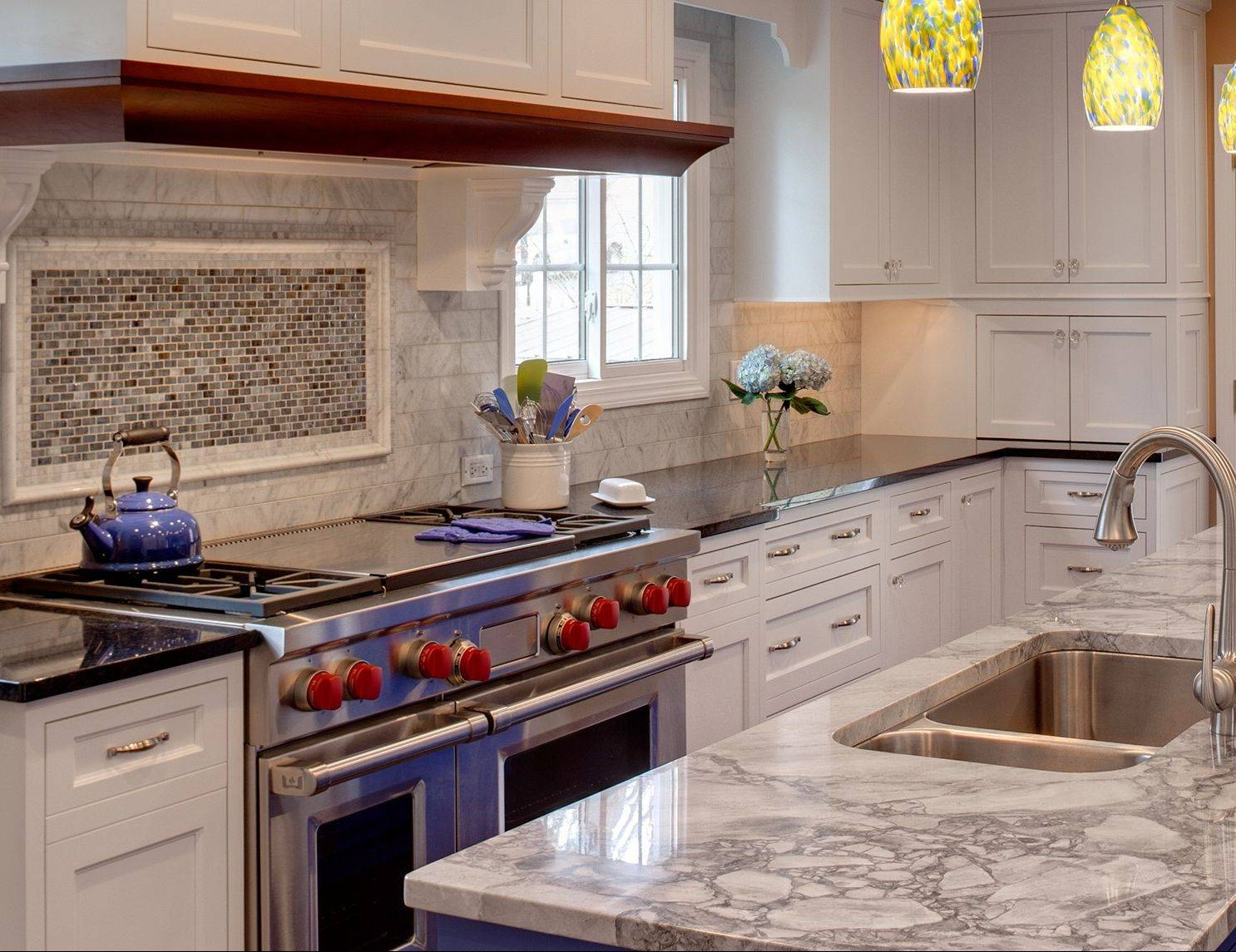 Terry Kenney decided white perimeter cabinets and a gray and white granite island countertop help subdue the blue of the island cabinets.