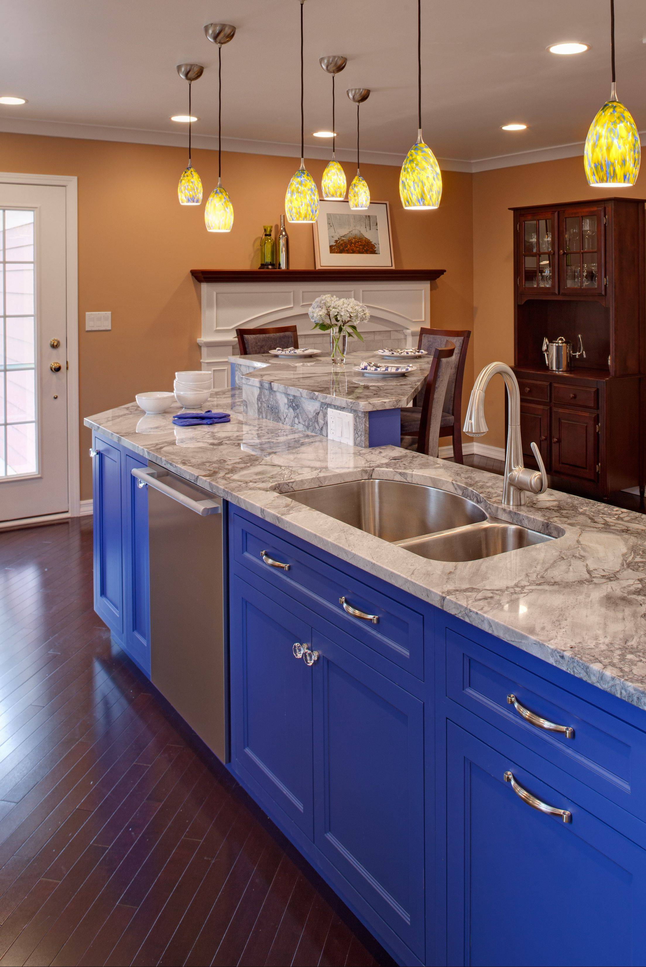 Terry Kenney fulfilled her Wheaton clients' wishes for really, really blue cabinets, above. Kenney balanced out the color with white perimeter cabinets and a gray-and-white countertop, below.