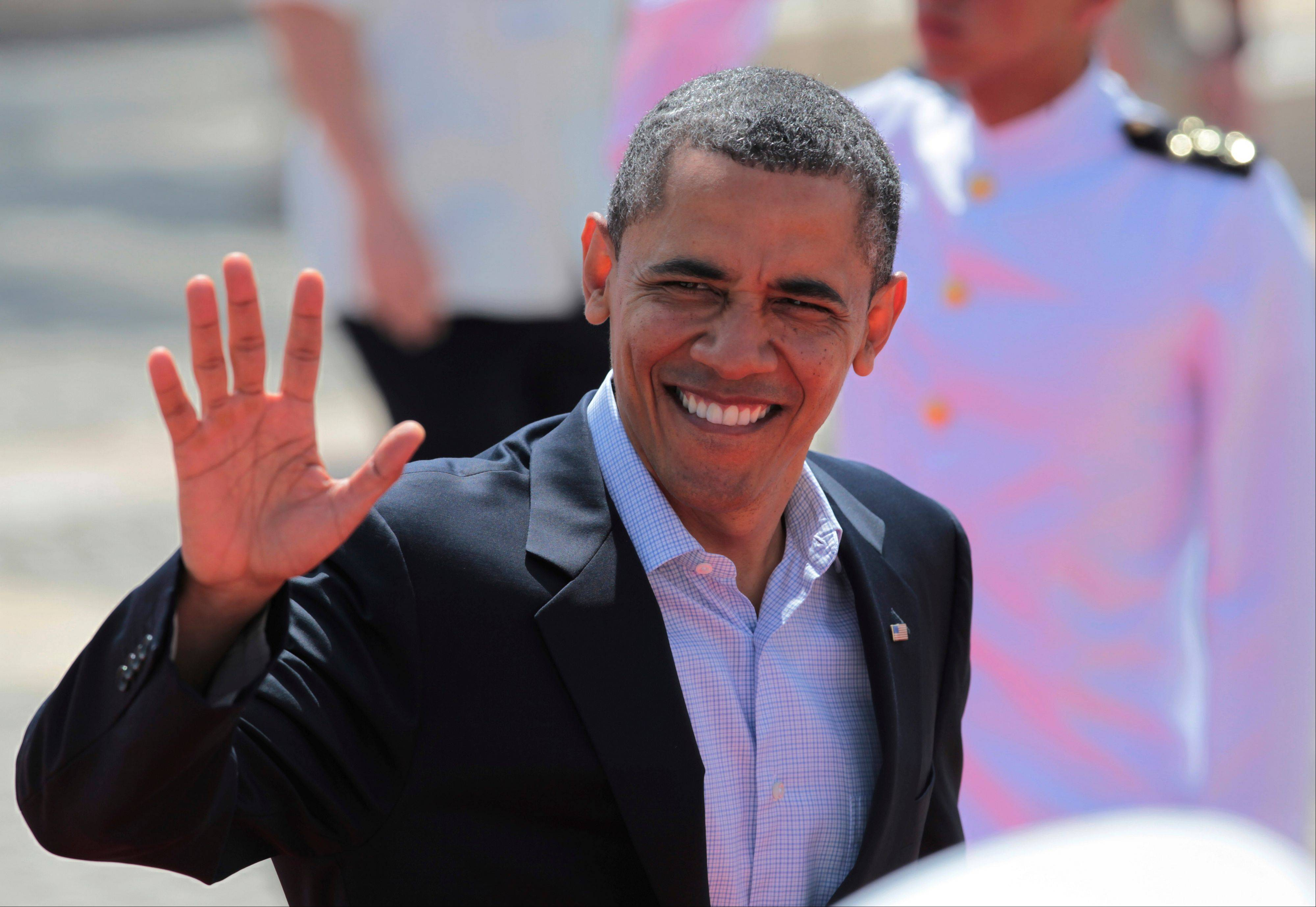 President Barack Obama waves as he arrives Sunday at the Convention Center for the second working session of the sixth Summit of the Americas in Cartagena, Colombia.