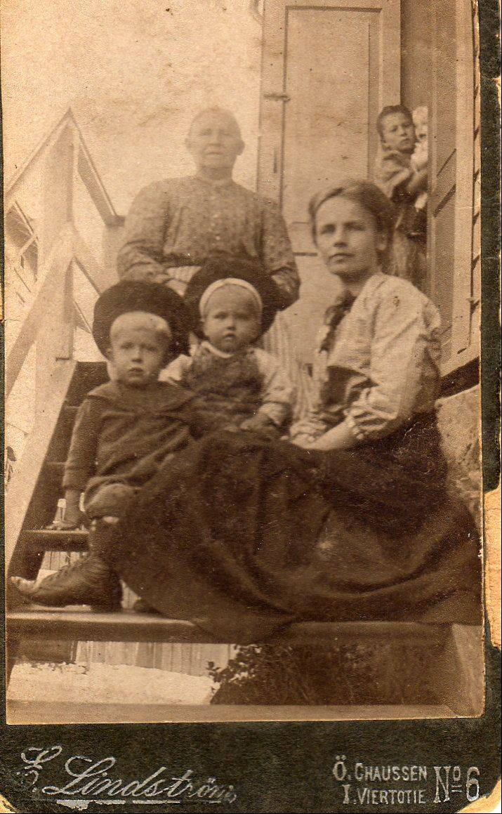 This image was made as Alice Johnson visited family in Finland. At bottom left is Alice's son Harold. Above right, Alice is holding daughter Eleanor in the doorway. Alice and the children would have left for home before the Titanic sailed, but the kids got chickenpox and couldn't travel. The family had stayed nine months in Finland, and also visited Oscar's family in Sweden. This photo was mailed home to husband and father Oscar in St. Charles.