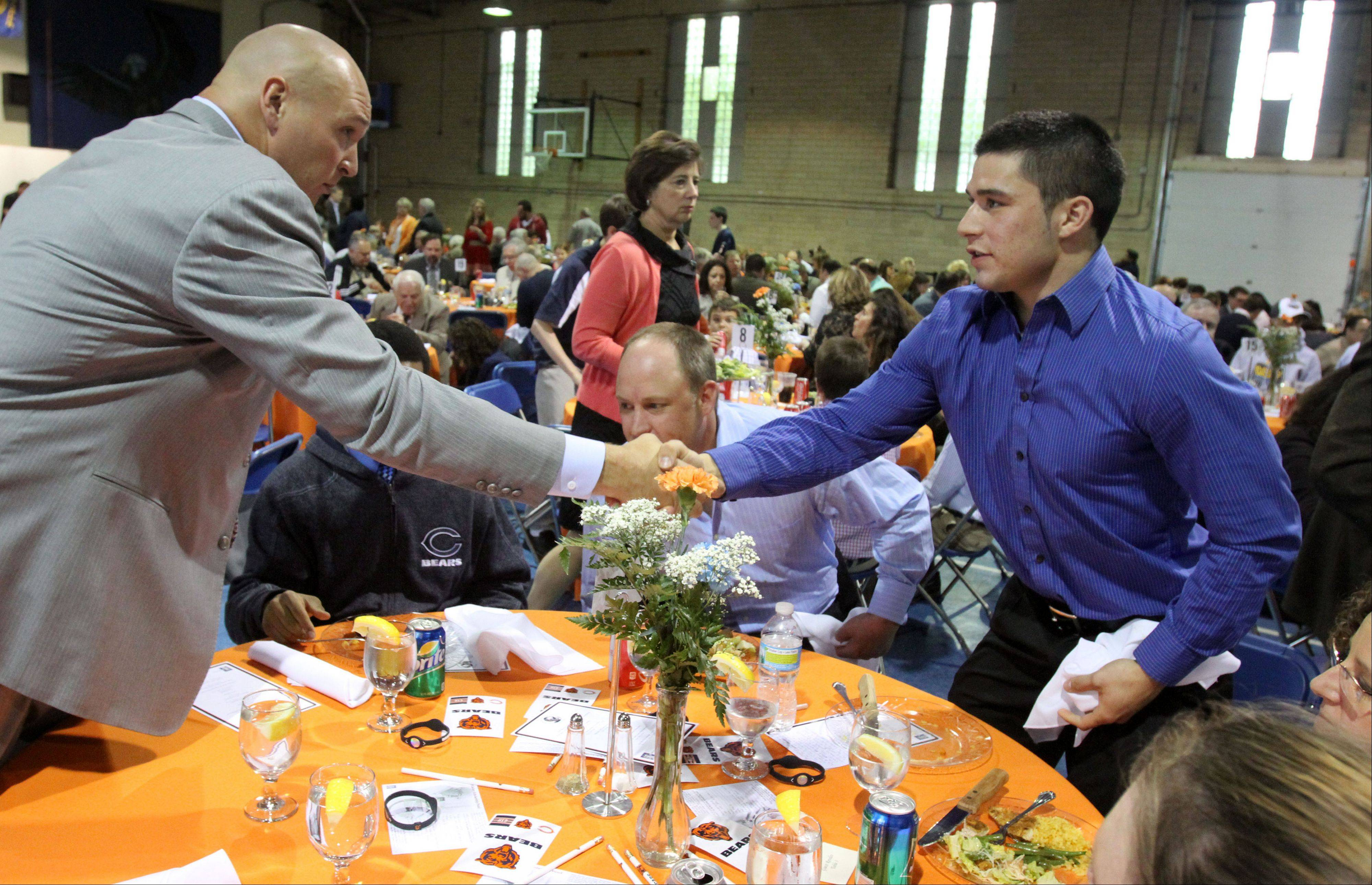 David Reveles of Naperville, a Maryville alumnus, received a Maryville scholarship and a handshake from Brian Urlacher.