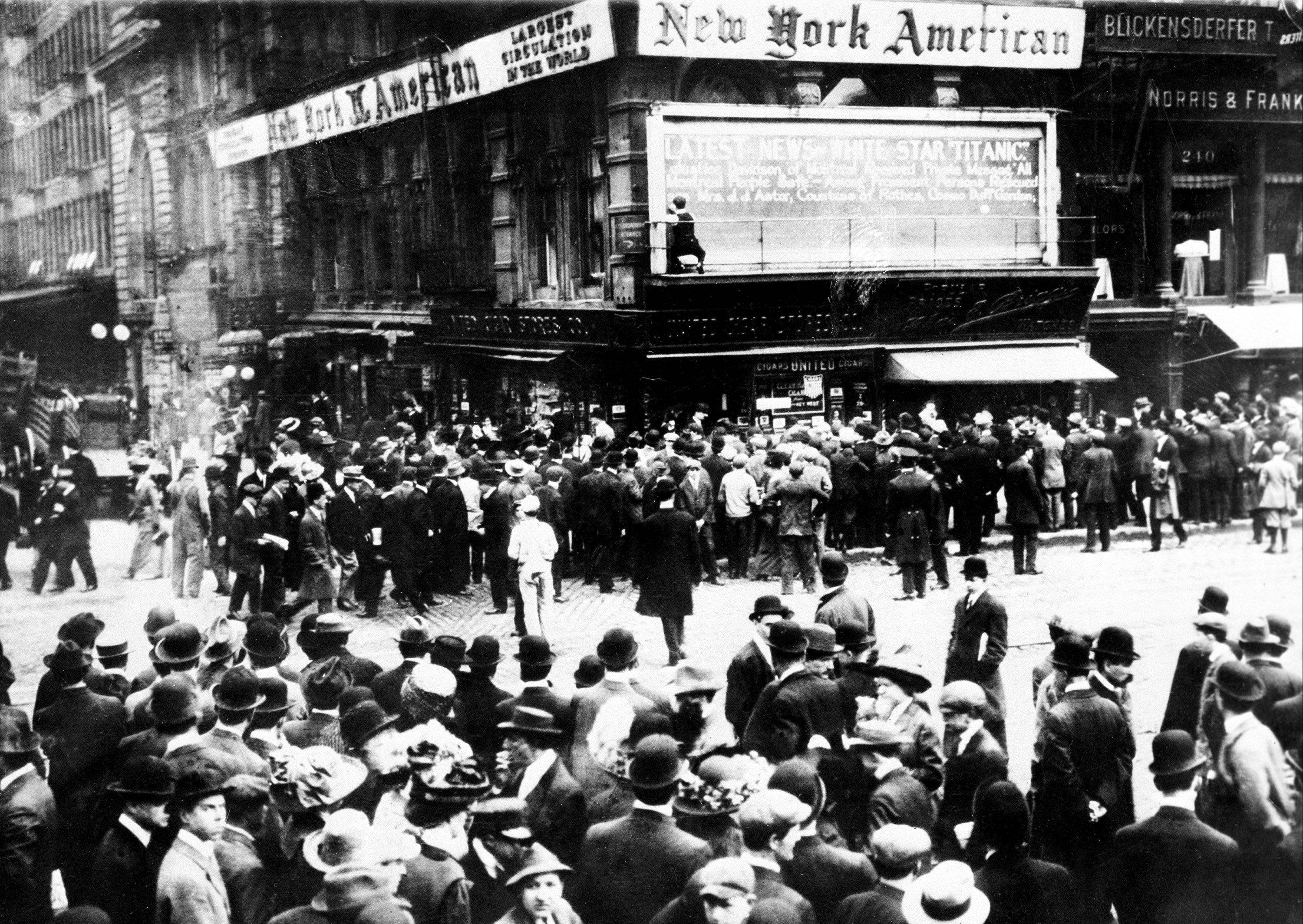 Crowds gather in April 1912 around the bulletin board of the New York American, where the names of people rescued from the sinking Titanic are on display just days after its sinking.
