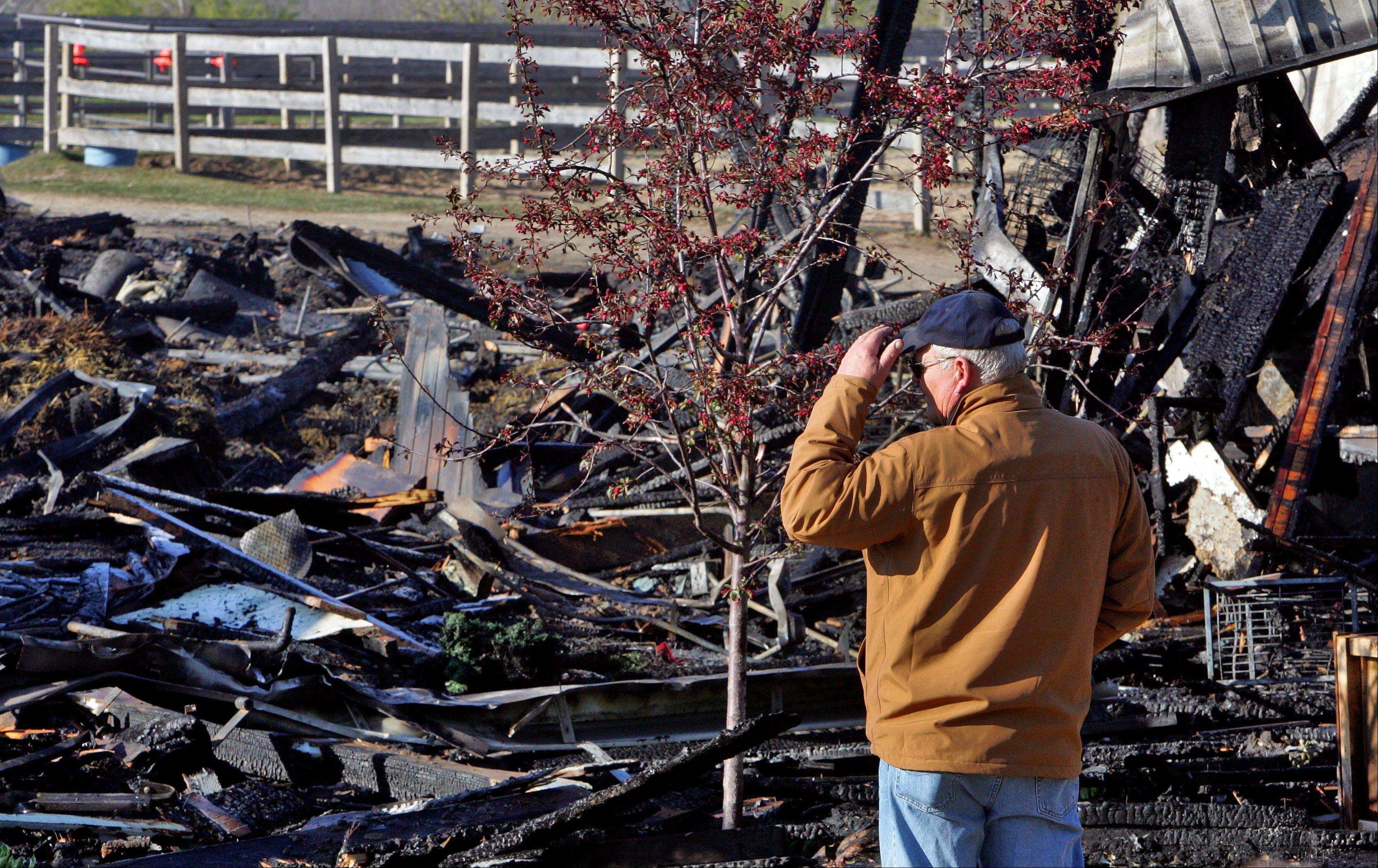People survey the wreckage the morning after a fire destroyed Black Tie Stable and killed several horses just West of Fox Lake in McHenry County Thursday.