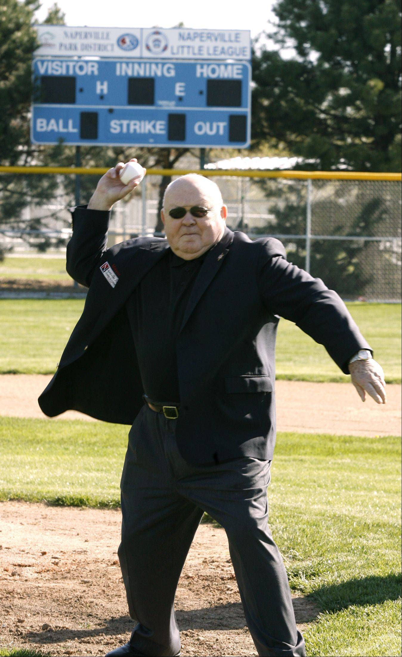 Naperville Mayor George Pradel throws out a first pitch, as the Naperville Park District celebrates the grand reopening of its recently renovated Knoch Park, and the opening of Naperville Little League's 60th season.